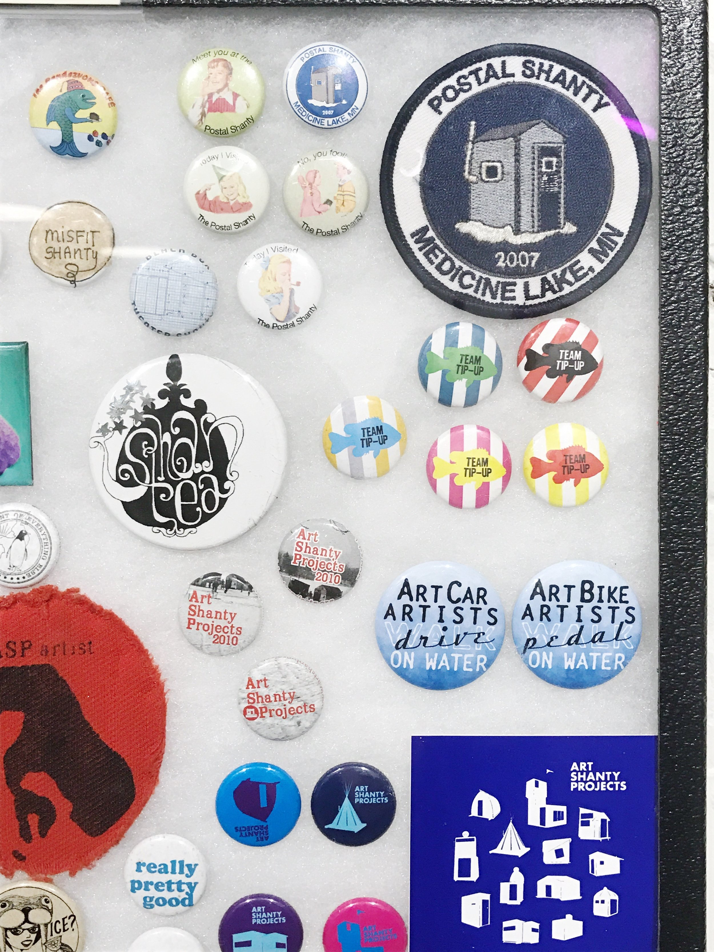 Some pins, patches and bumper stickers, commemorating Art Shanties of years past.