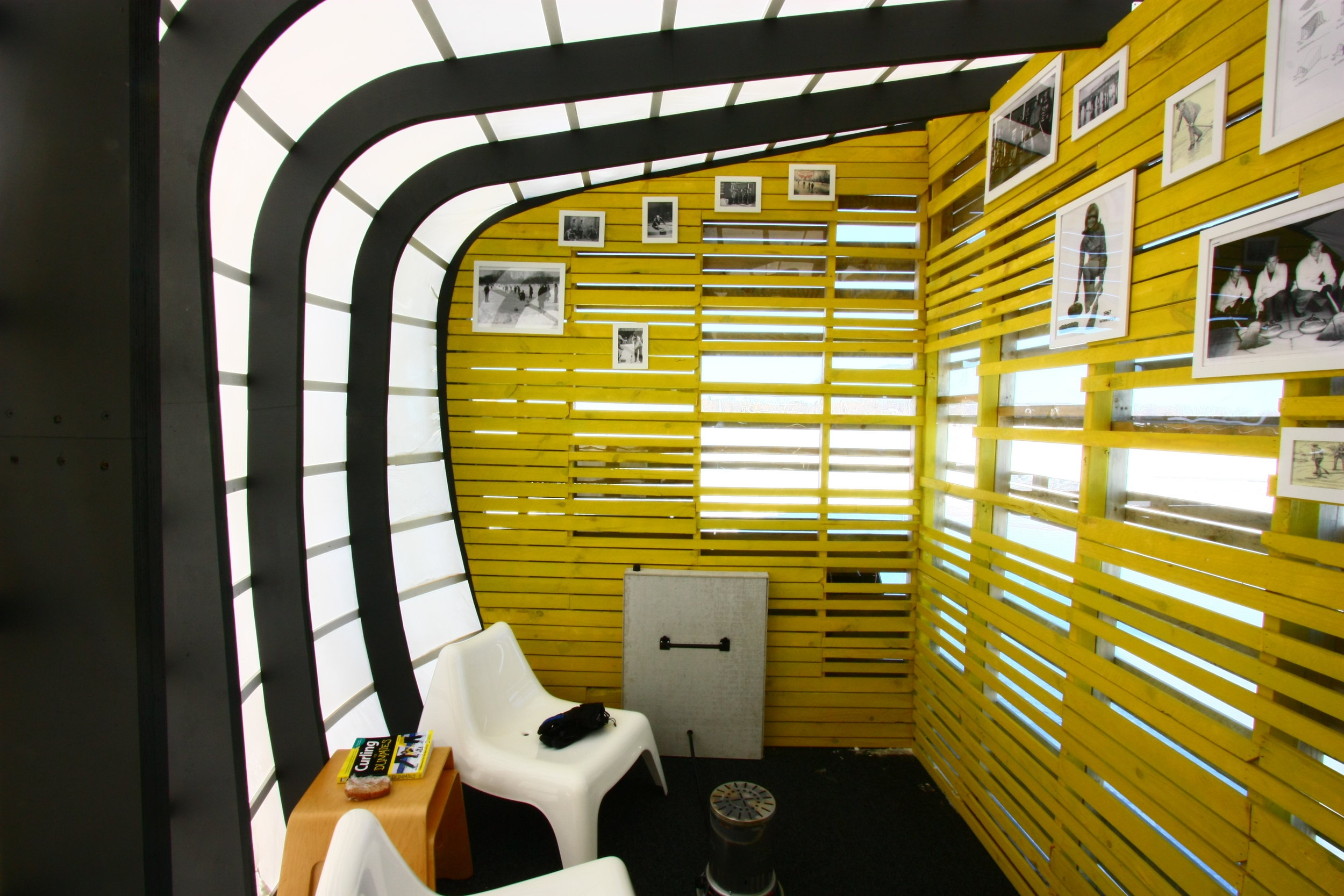 Warm interior of curling-themed art shanty designed by NewStudio Architecture