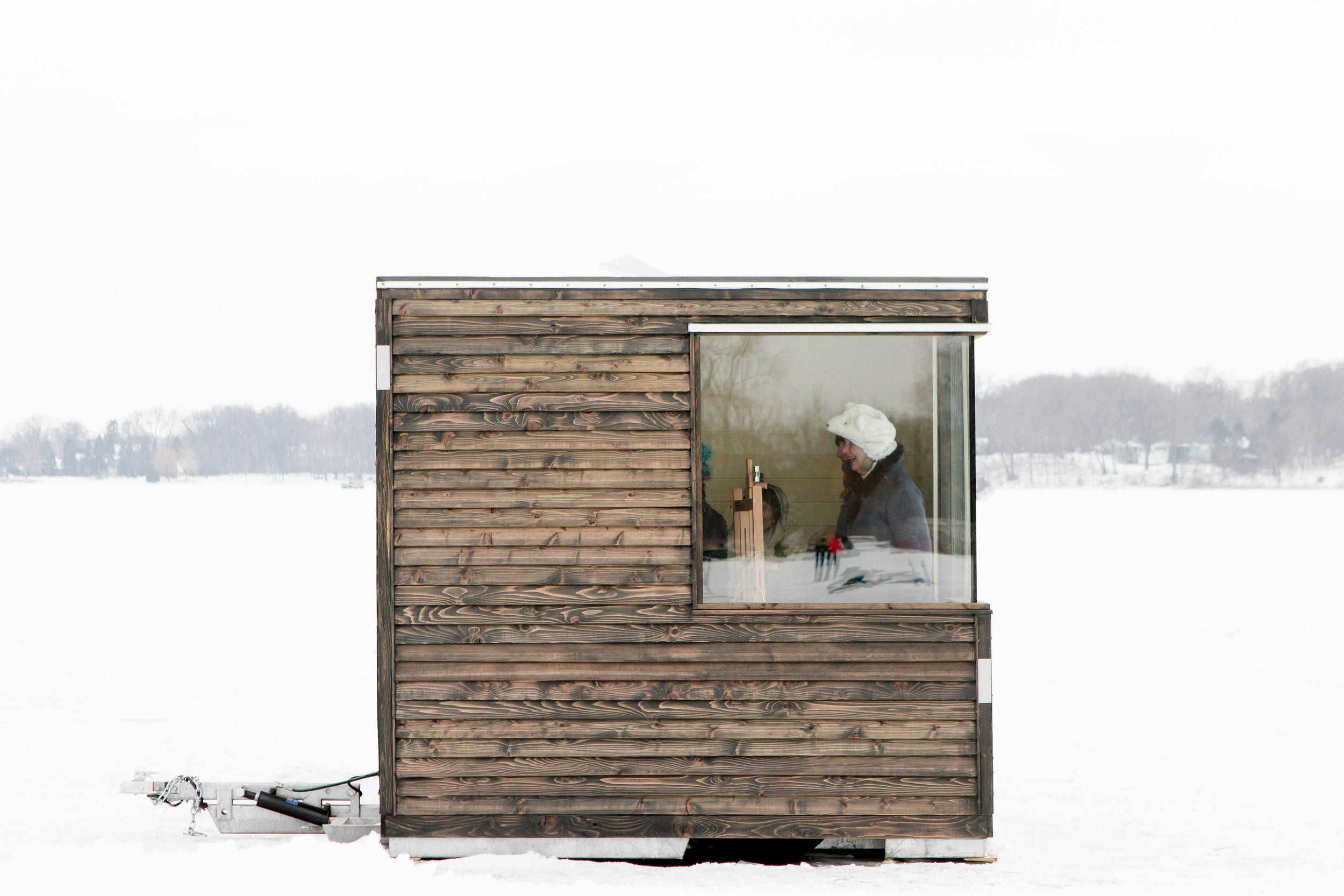 Exterior view shows an artist working inside the art shanty designed by NewStudio Architecture