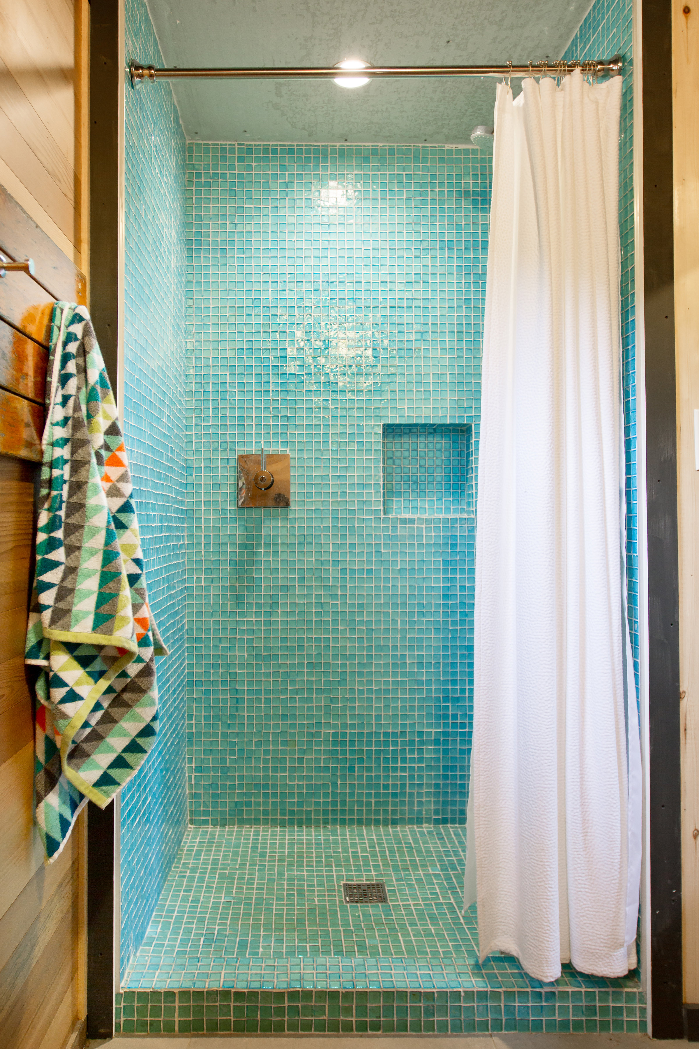 Aqua shower tile in mid-century modern boathouse designed by NewStudio Architecture