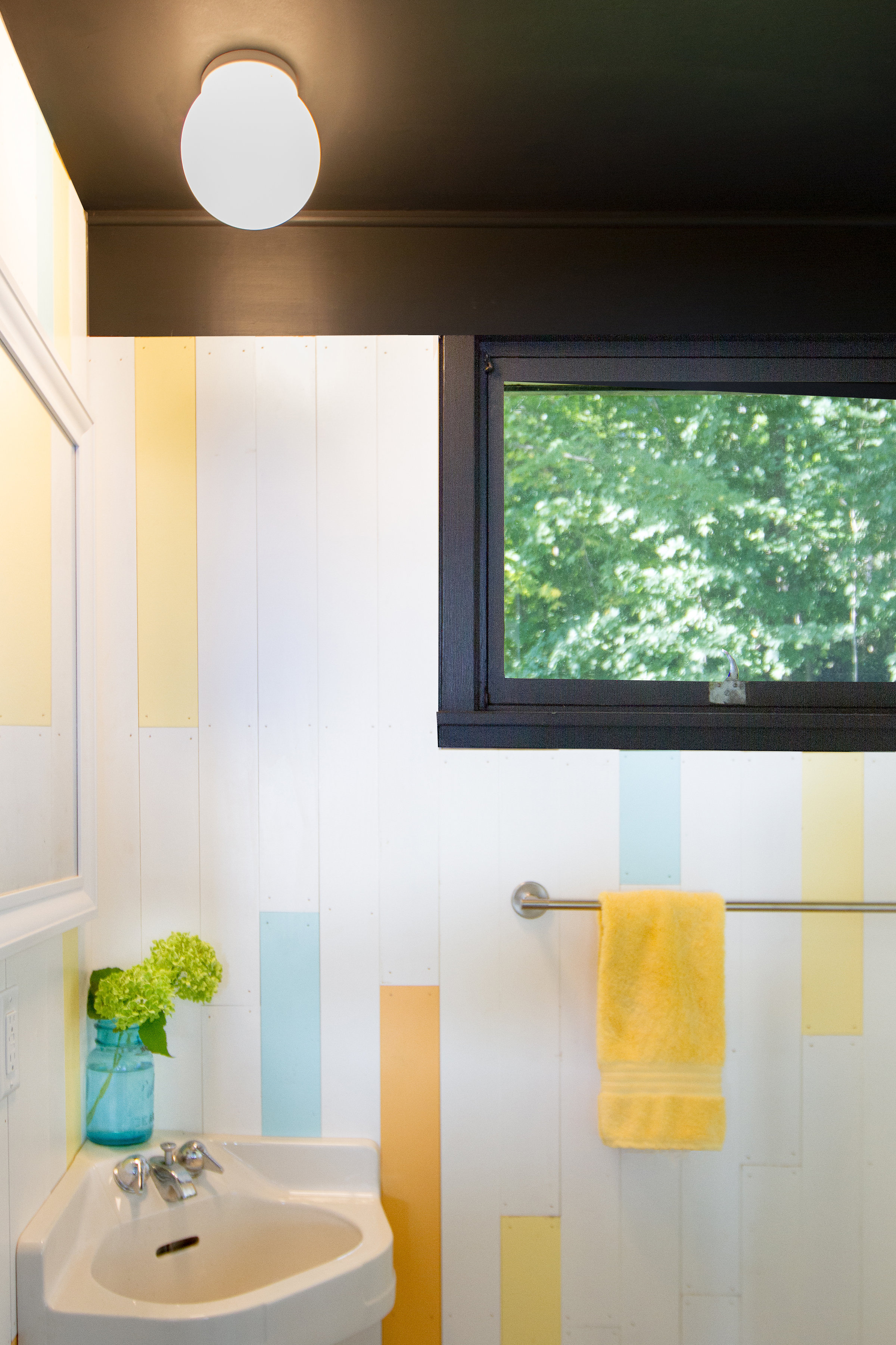 Charcoal trim contrasts white, aqua, yellow, and orange accents; designed by NewStudio Architecture