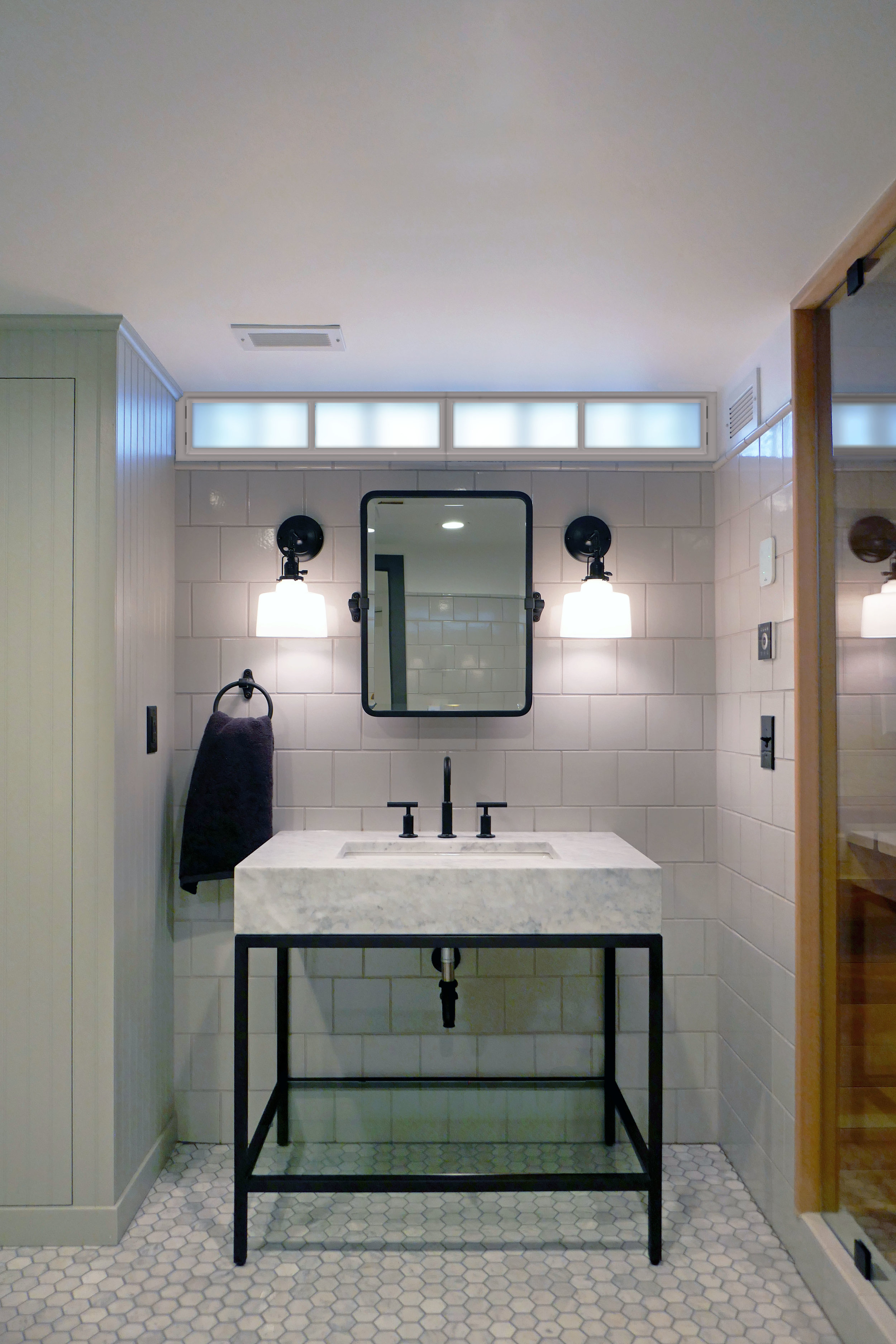 A clean and modern bathroom remodel by NewStudio Architecture blends with the home's early 20th century aesthetic.
