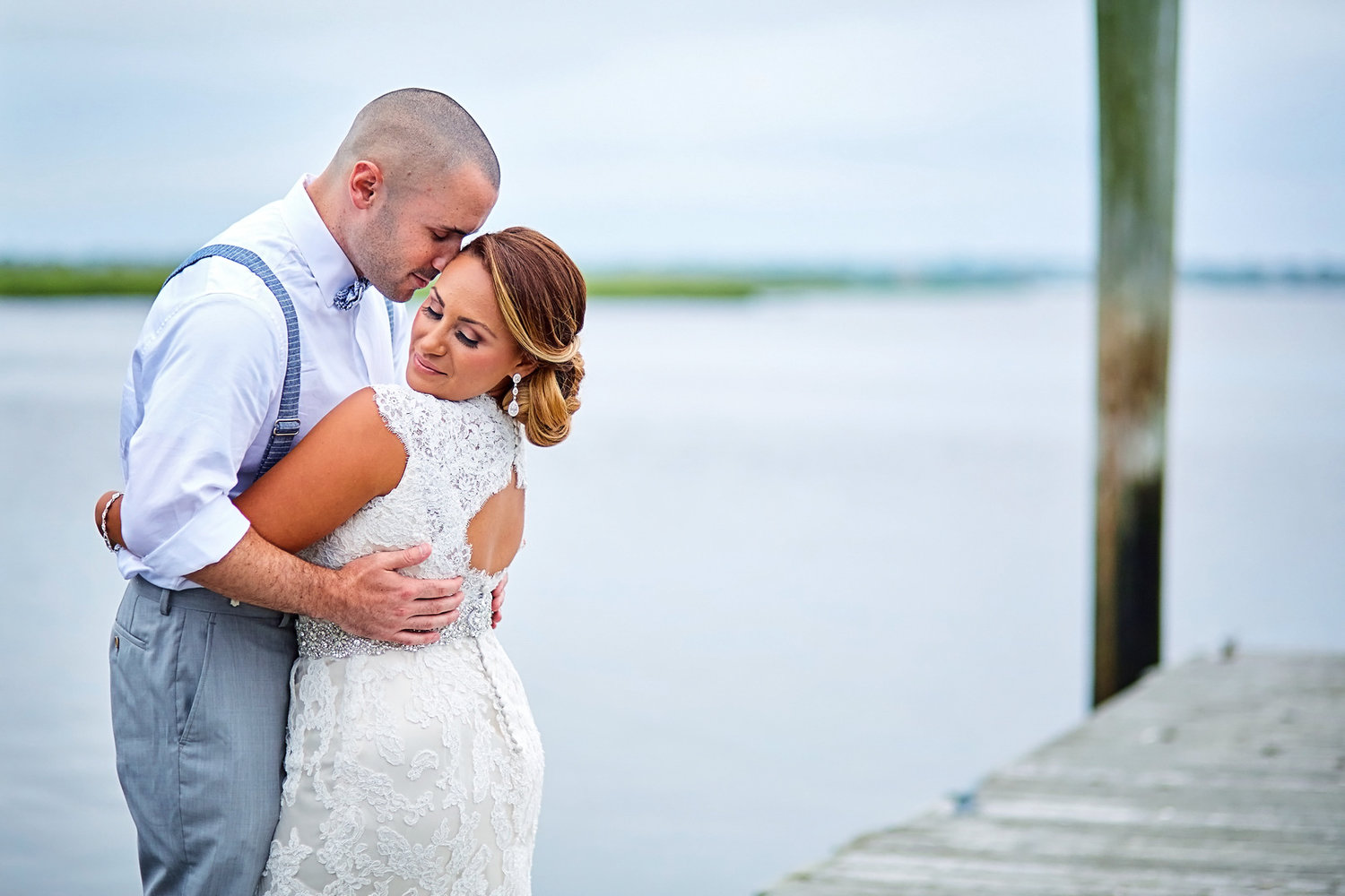 Casual bride and groom embrace on a waterside dock in Long Island, New York.