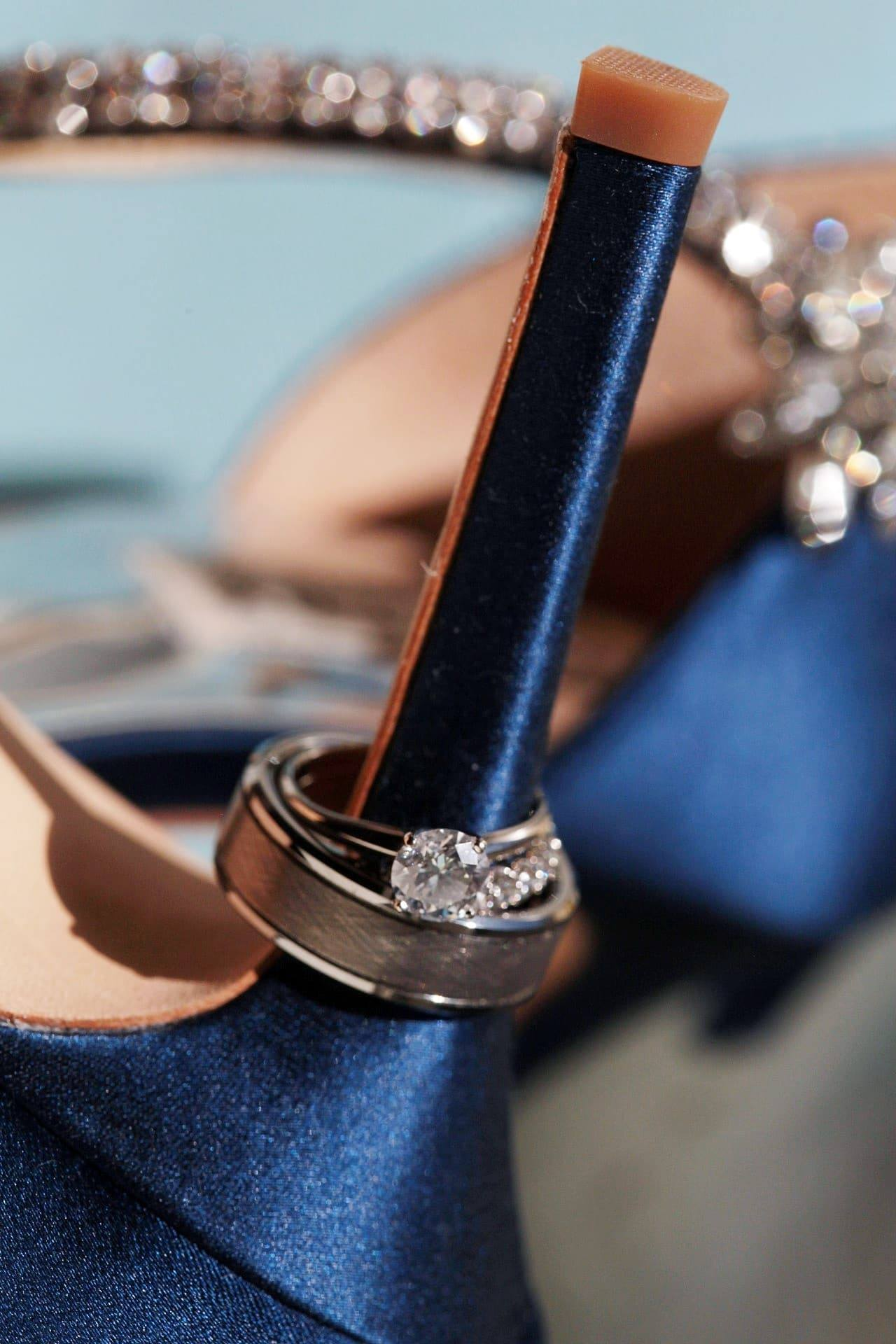 Wedding bands and diamond engagement ring displayed on heel of blue wedding shoe at the Gastonian Inn, Savannah, Georgia.