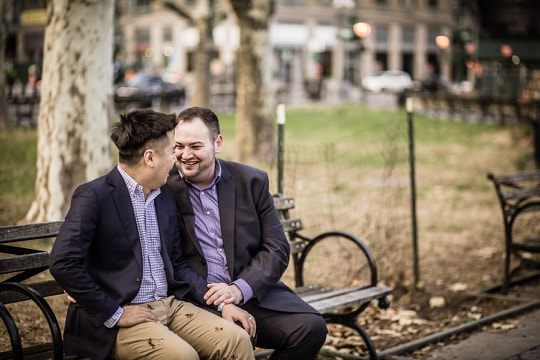 Two grooms sit on a park bench, downtown, after their LGBTQ same sex wedding at City Hall.