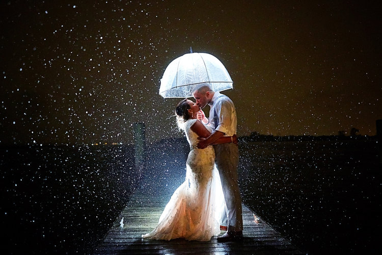Nighttime backlit rain portrait of bride and groom under an umbrella on a dock.