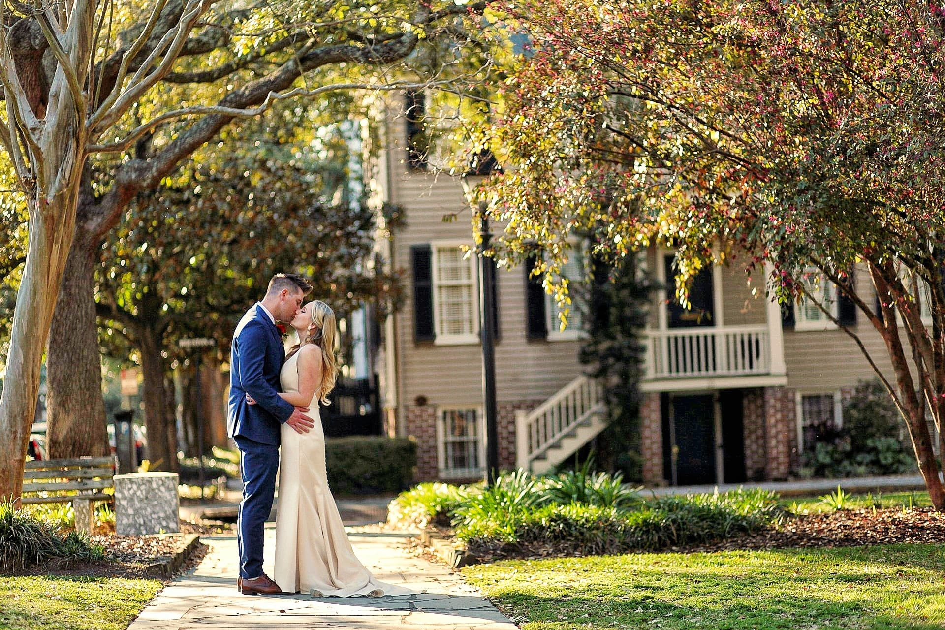 Bride and groom kiss in Washington Square, by the Brice Hotel in Savannah, Georgia.