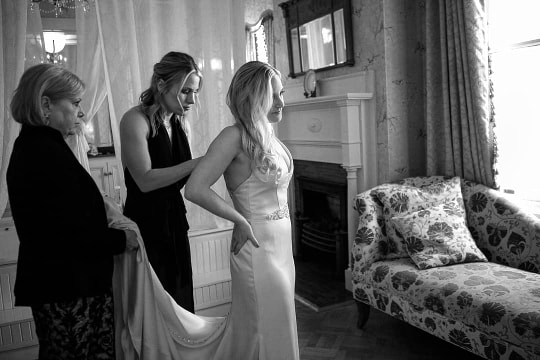 Sister and mother help bride put on her wedding dress, in natural light in the bridal suite at Gastonion Inn, Savannah, Georgia