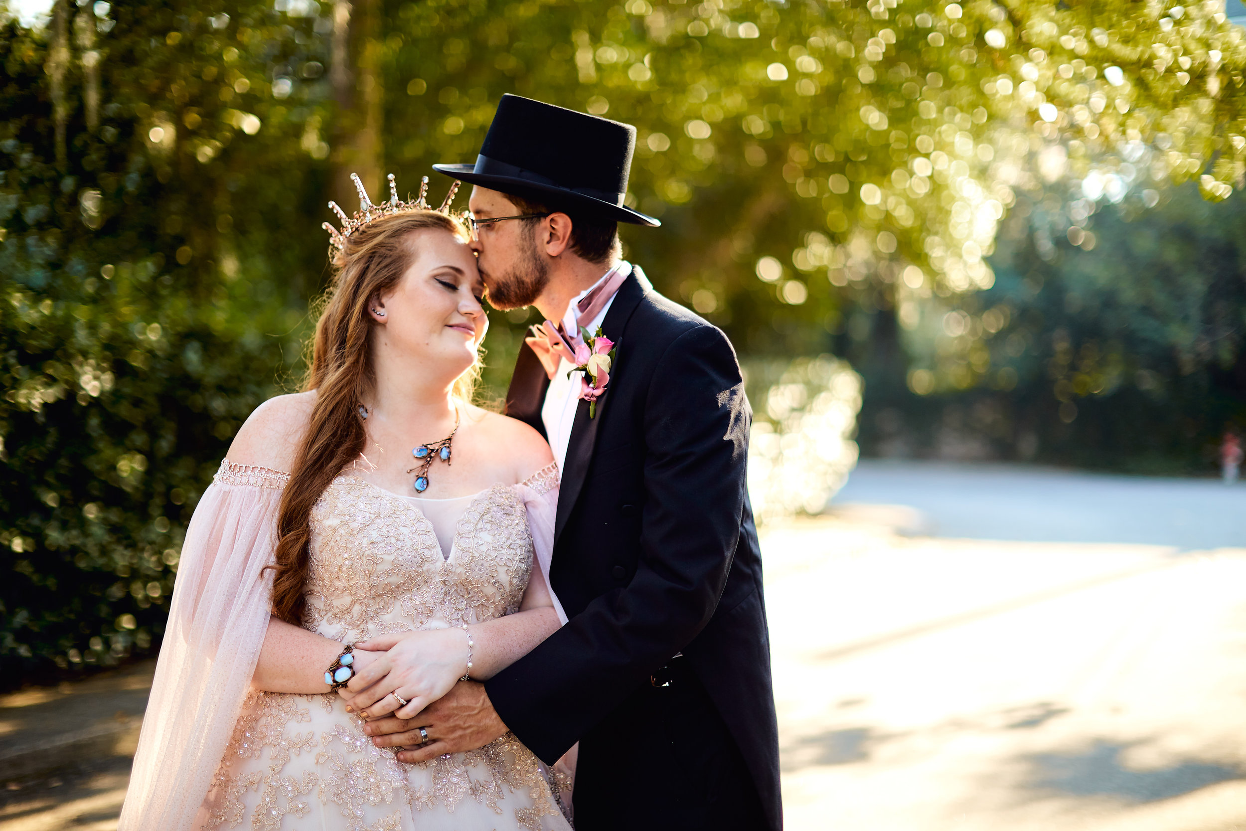 Whimsical golden hour portrait of offbeat bride and groom, where bride wears blush dress with DIY cape, and groom wears top hat. on the street by downtown Beaufort, South Carolina.