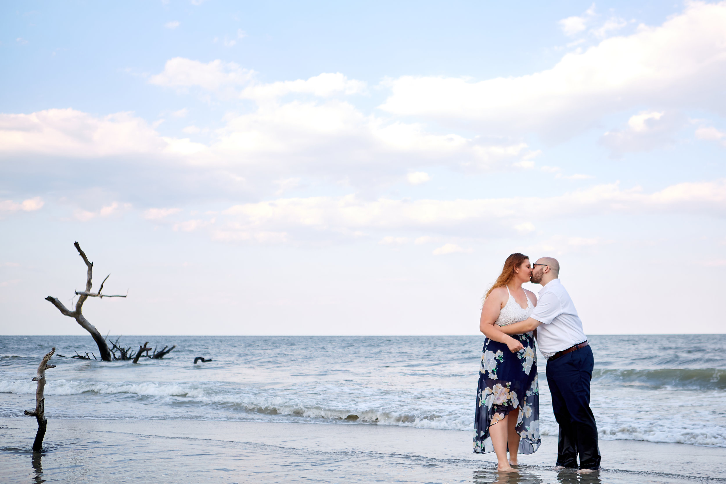 Engagement session with kissing couple, in the water with tree, at Hunting Island State Park, Beaufort County, South Carolina.