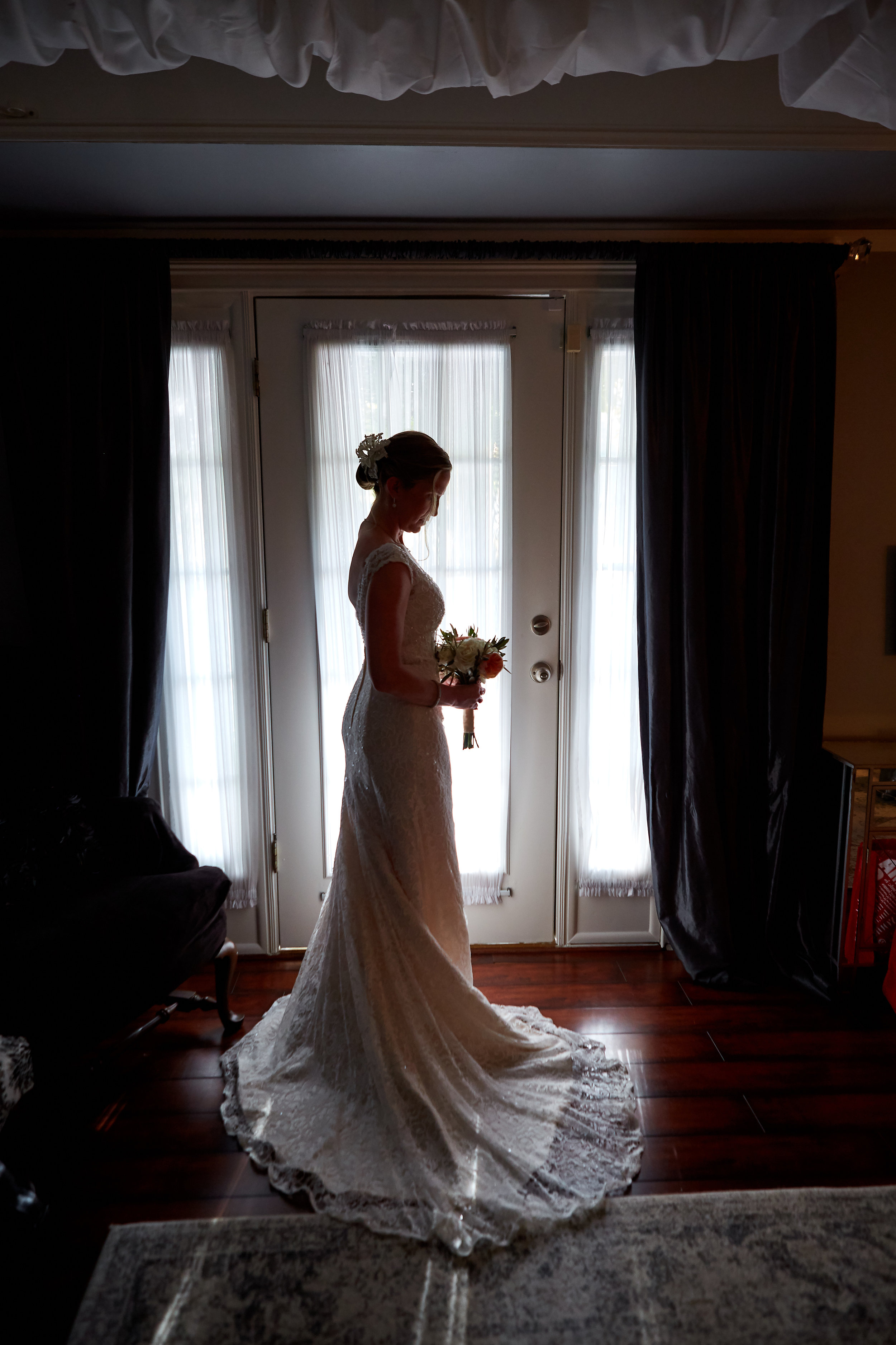 Silhouette portrait of a bride in her wedding dress, looking at her bouquet, at the Mackey House bridal suite, Savannah, Georgia.