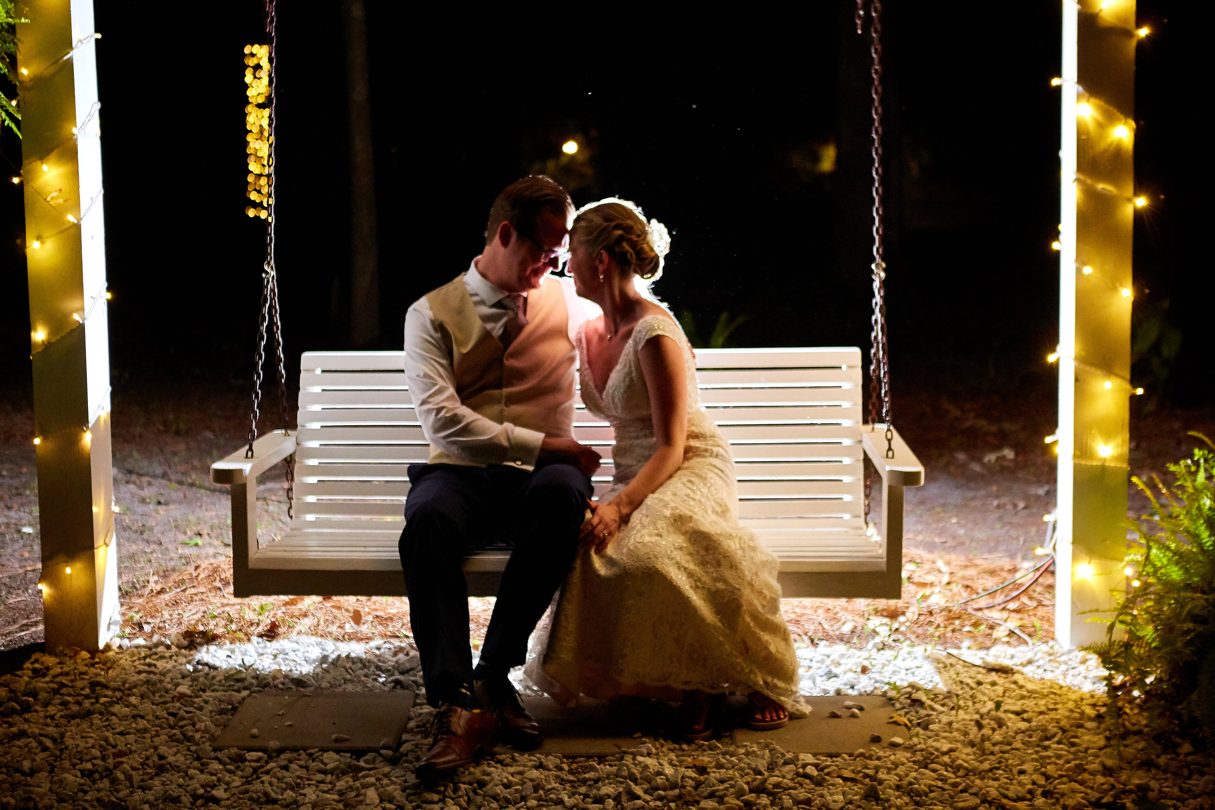 Nighttime, backlit portrait of bride and groom sitting on a swing at the Mackey House, in Savannah, Georgia.