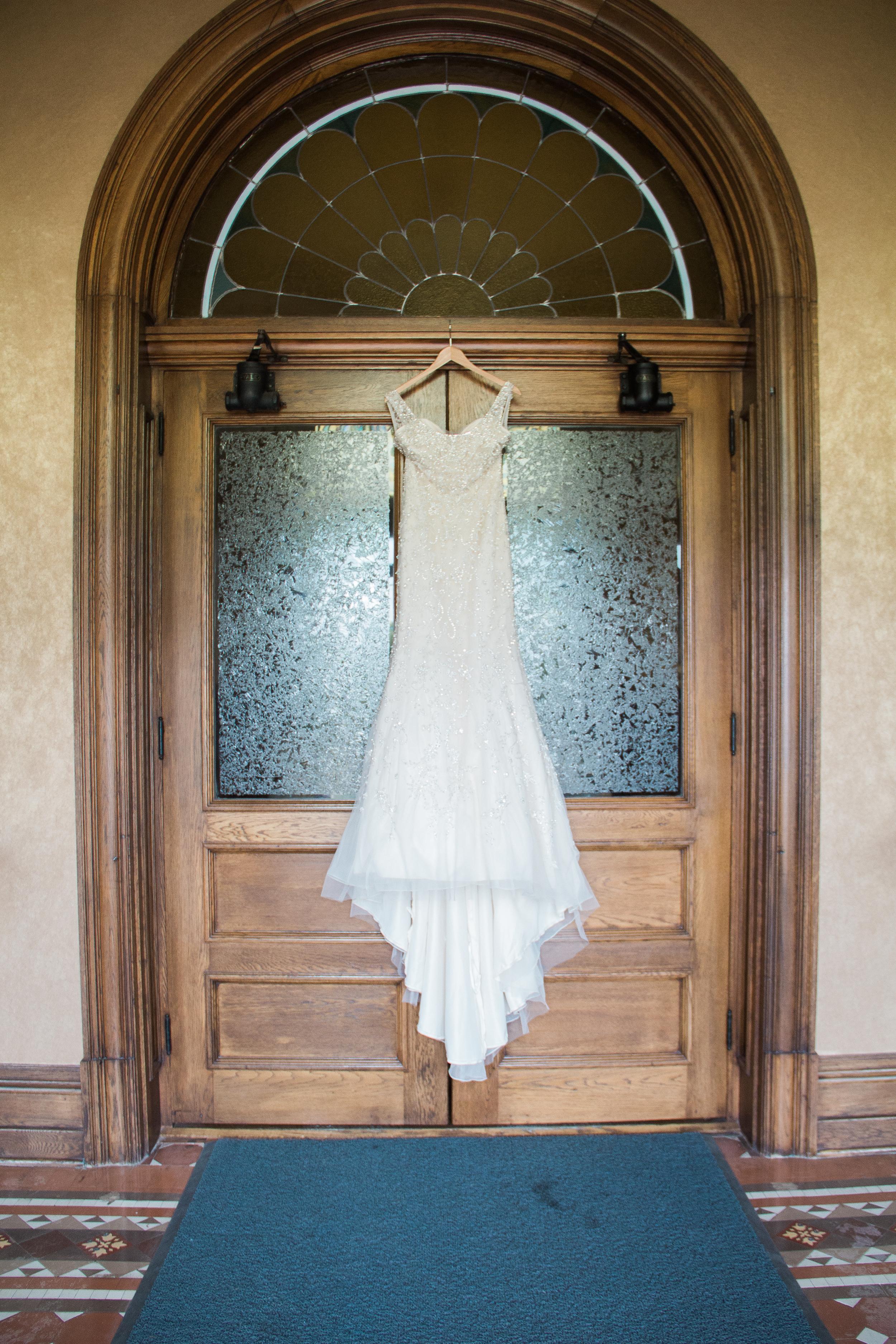 Wedding dress hanging in church doorway for classic wedding in New Prague Minnesota