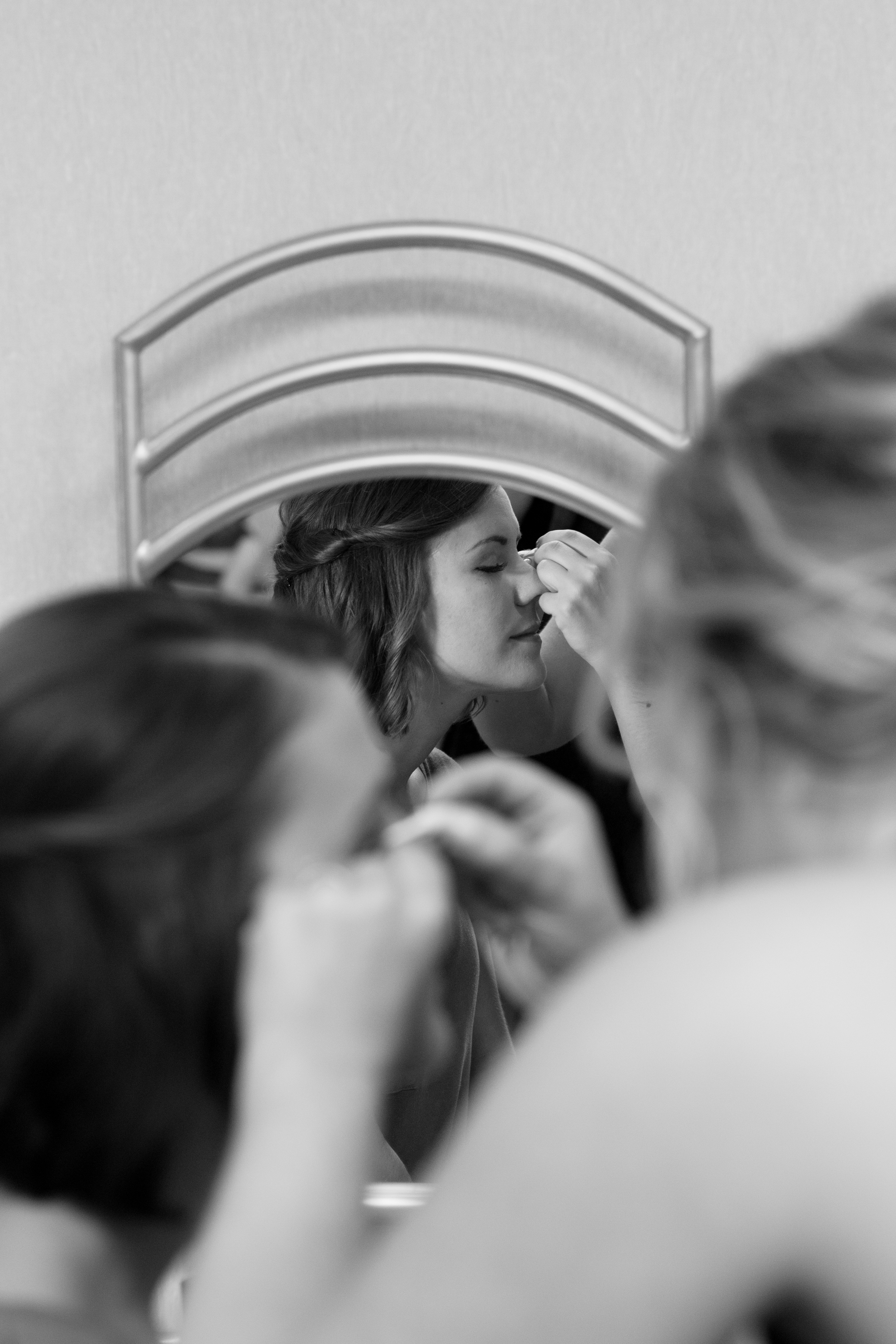 Bride getting ready for wedding day, black and white photo of bride in mirror at wedding at Brackett's Crossing Country Club in Lakeville Minnesota
