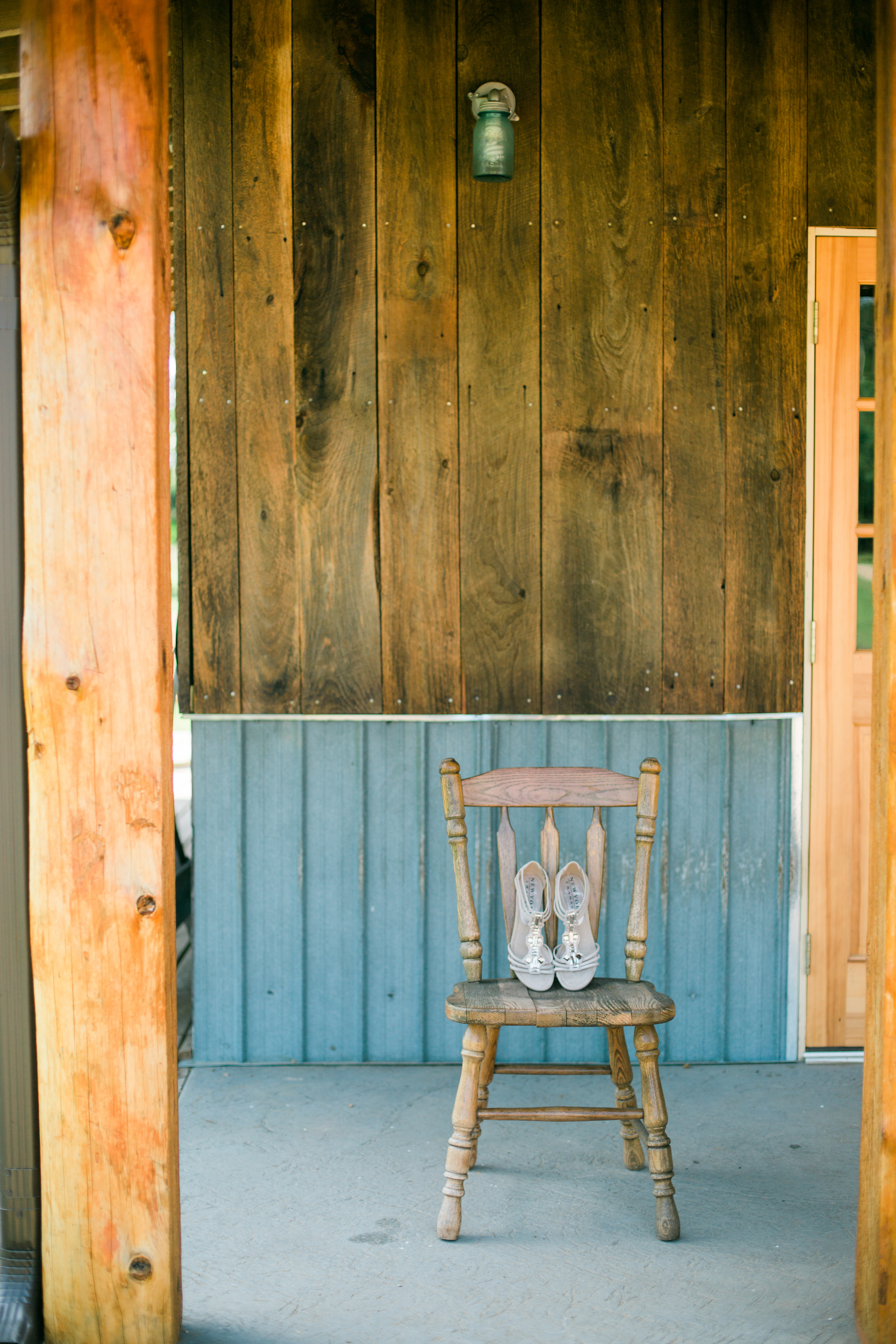 Bride's shoes on farmhouse chair at the rustic Echo Valley in Wisconsin with barnwood and galvanized metal backdrop