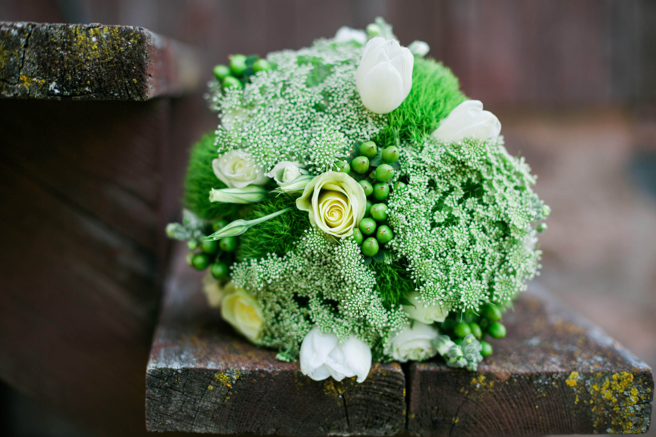 Bride's bouquet with greens sitting on barn step at rustic Echo Valley wedding in Wisconsin