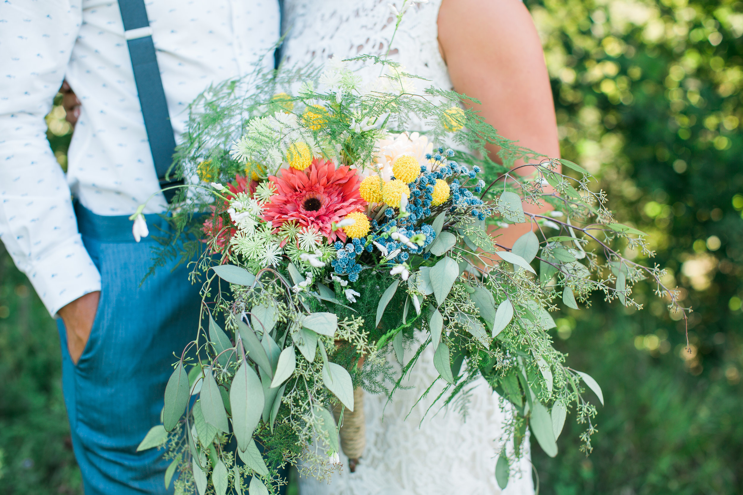 Bride and groom with wedding bouquet groom wearing suspenders rustic Minnesota wedding at The Outpost Center in Chaska Minnesota