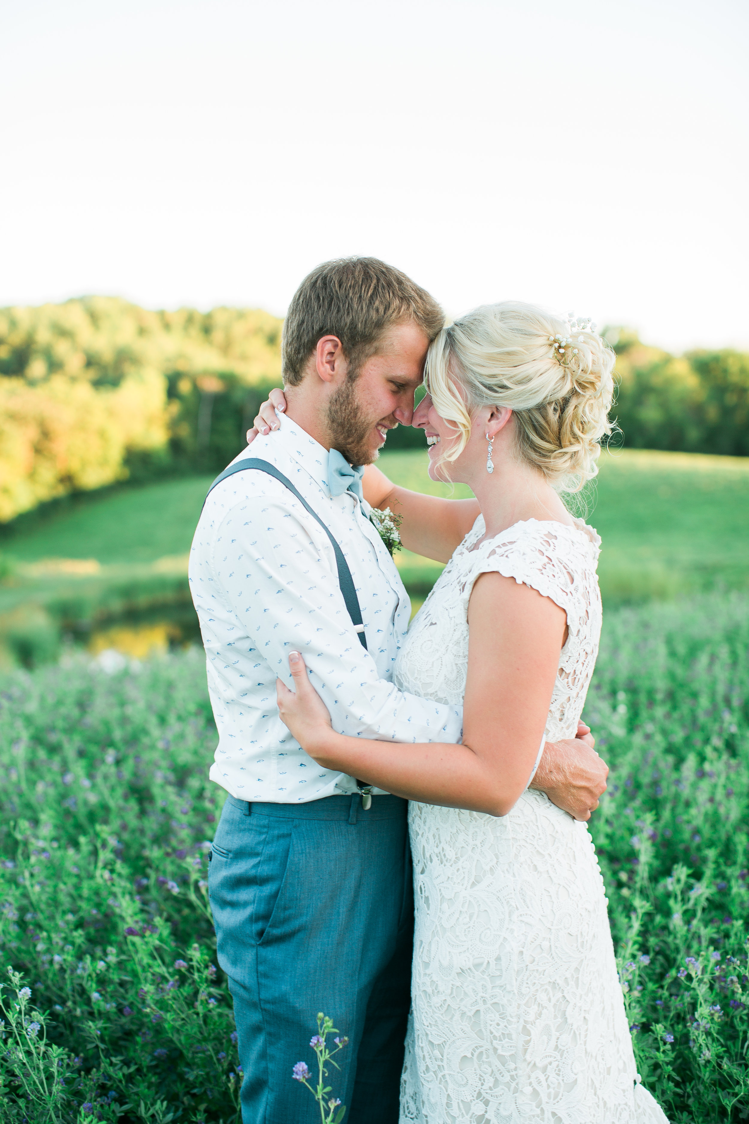 Bride and groom portrait in a field of flowers at The Outpost Center in Chaska Minnesota for rustic rural wedding