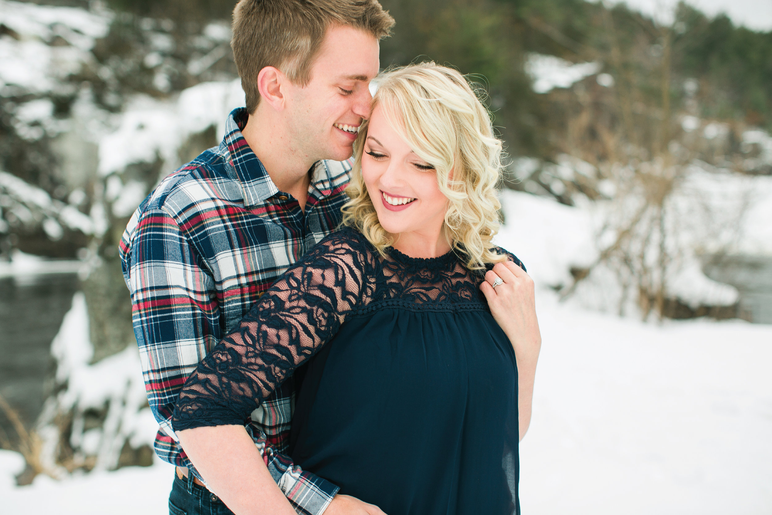 Minnesota snowy winter engagement photos in Taylors Falls Minnesota laughing in navy lace and plaid