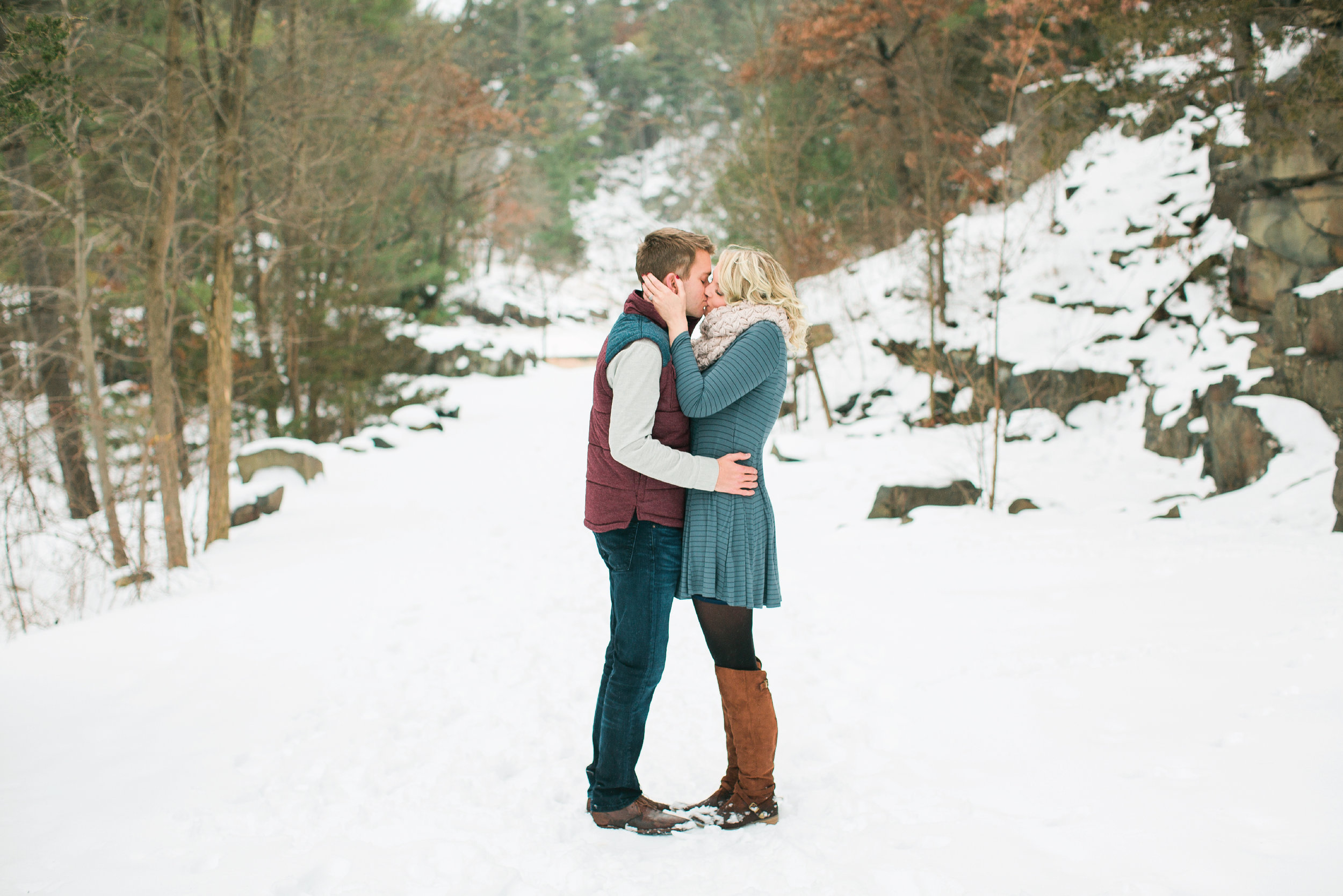 Taylors Falls Minnesota snowy winter engagement session in the woods with couple kissing