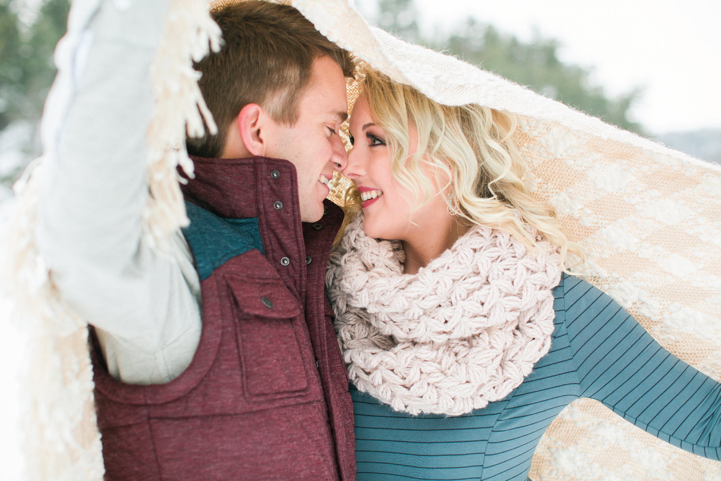 Taylors Falls Minnesota snowy winter engagement session with couple under blanket