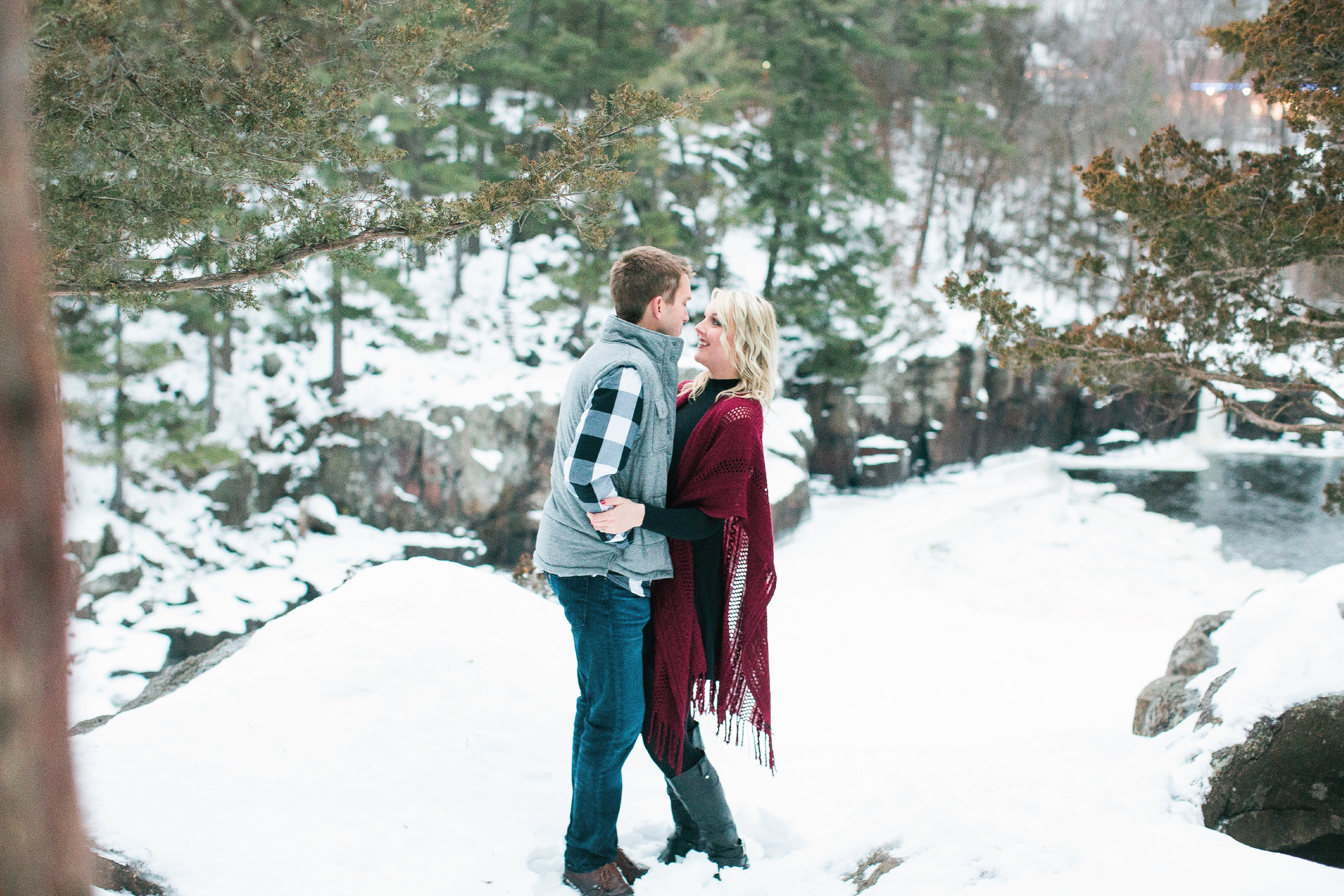 Snowy Minnesota Taylors Falls winter engagement photos on bluff overlooking river and woods in burgundy shawl, plaid vest