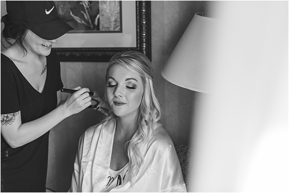 Minnesota summer wedding of bride getting makeup on in bridal robe in black and white