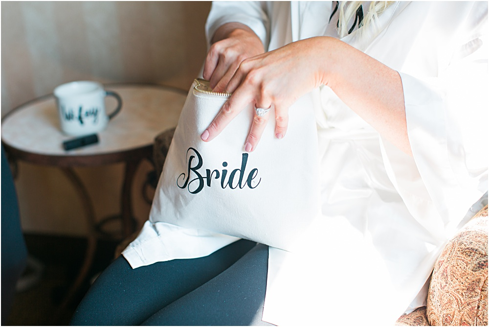 Minnesota summer wedding of bride getting makeup on in bridal robe with bride makeup bag