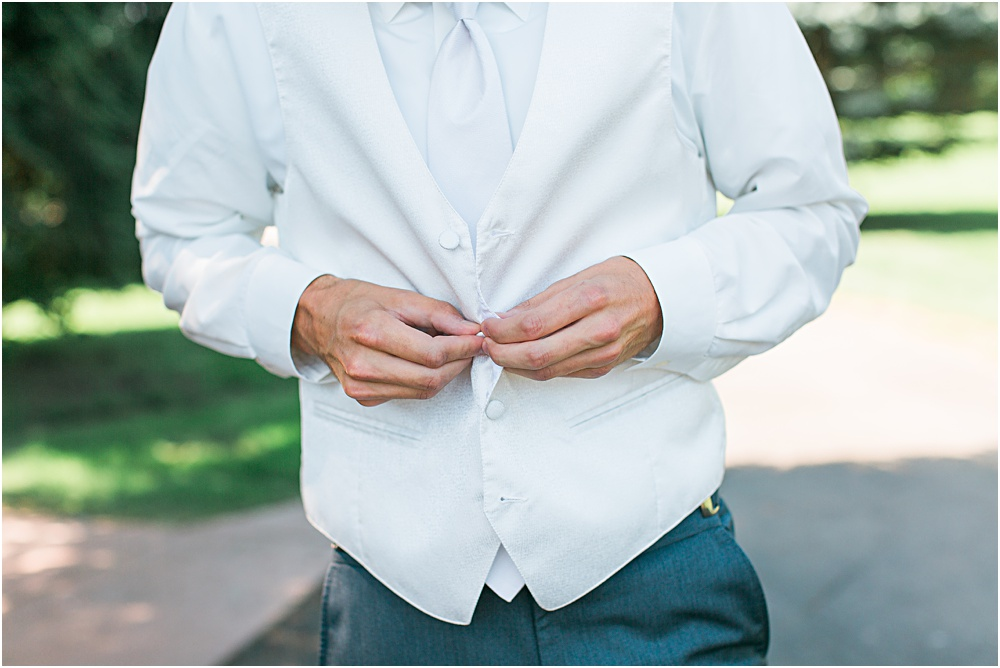 Groom getting ready for Minnesota summer wedding day in white vest