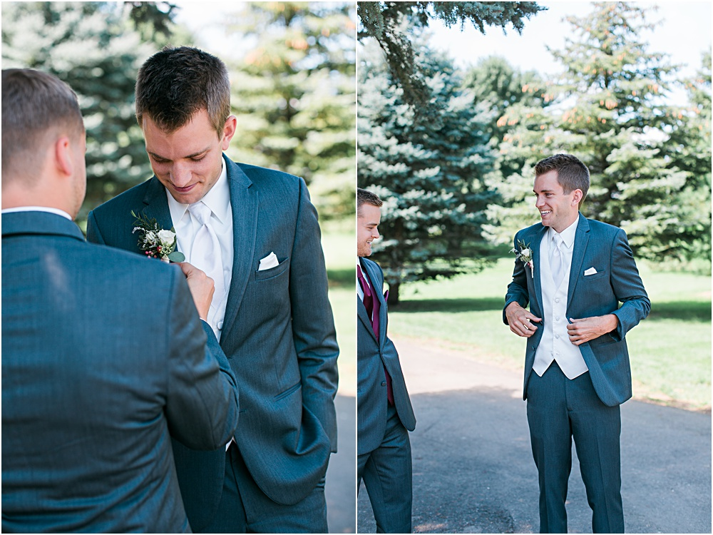 Groom getting ready for Minnesota summer wedding day in dark gray suit and white vest best man helping groom into suit