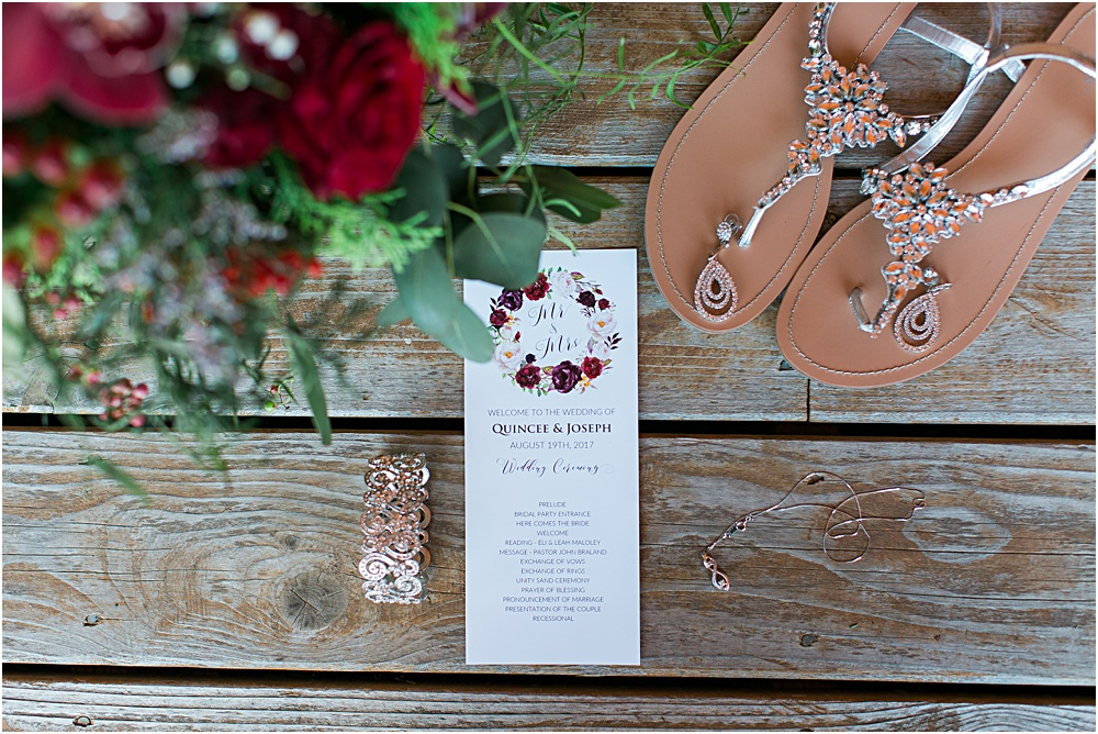 Minnesota summer wedding photo showing invitation, jewelry and shoes in burgundy wine color