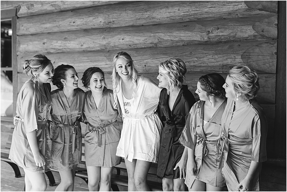 Minnesota summer wedding bride and bridesmaids laughing in coordinating robes in front of cabin in black and white