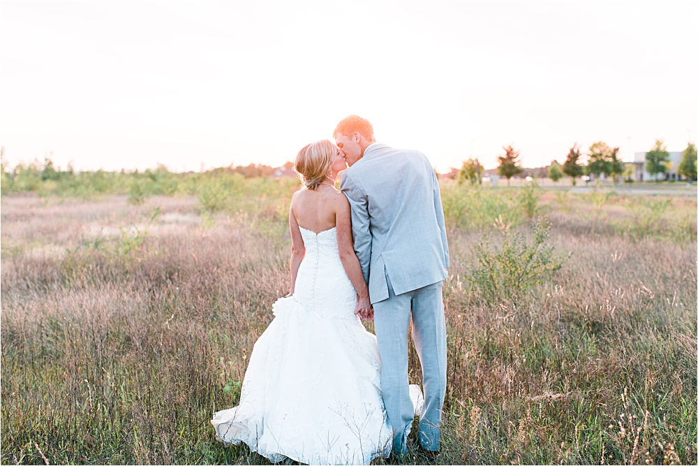 Bride and groom kissing in field during sunset of Minnesota summer wedding