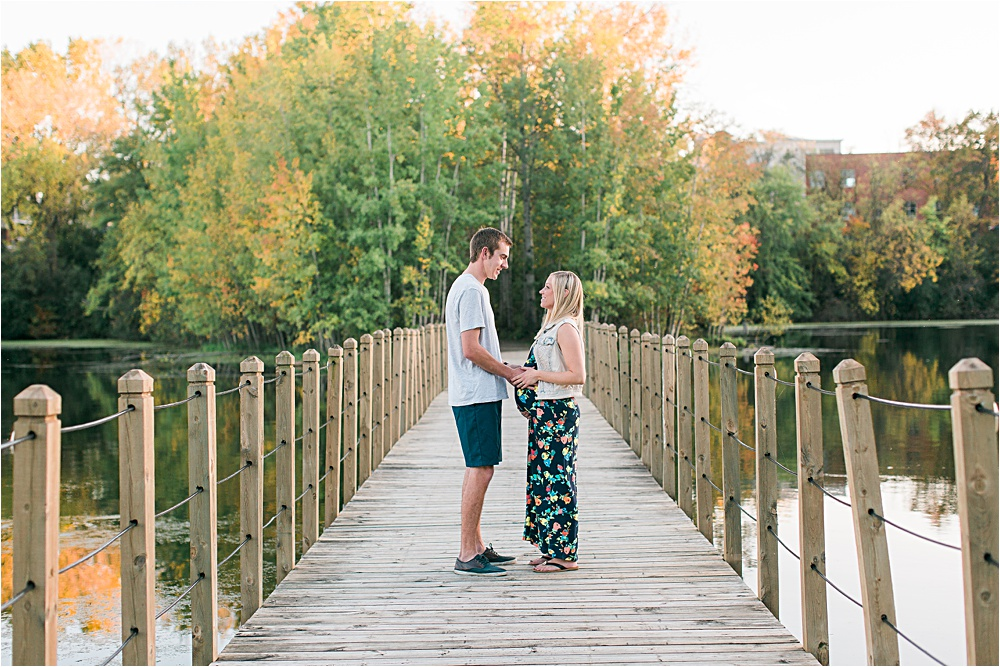 Husband and wife on bridge for fall Minnesota maternity photos showing bump with floral maxi dress and denim vest