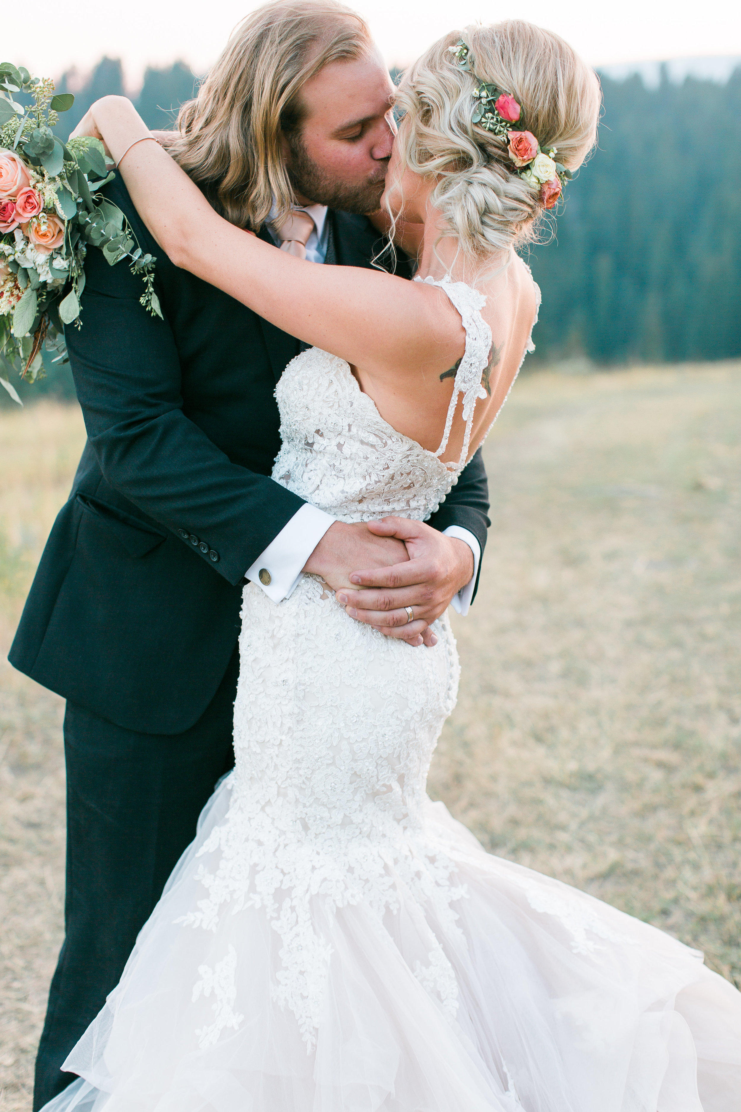 Bride and groom kissing in Big Sky Montana in front of mountains with floral crown and Madeline Gardner wedding dress