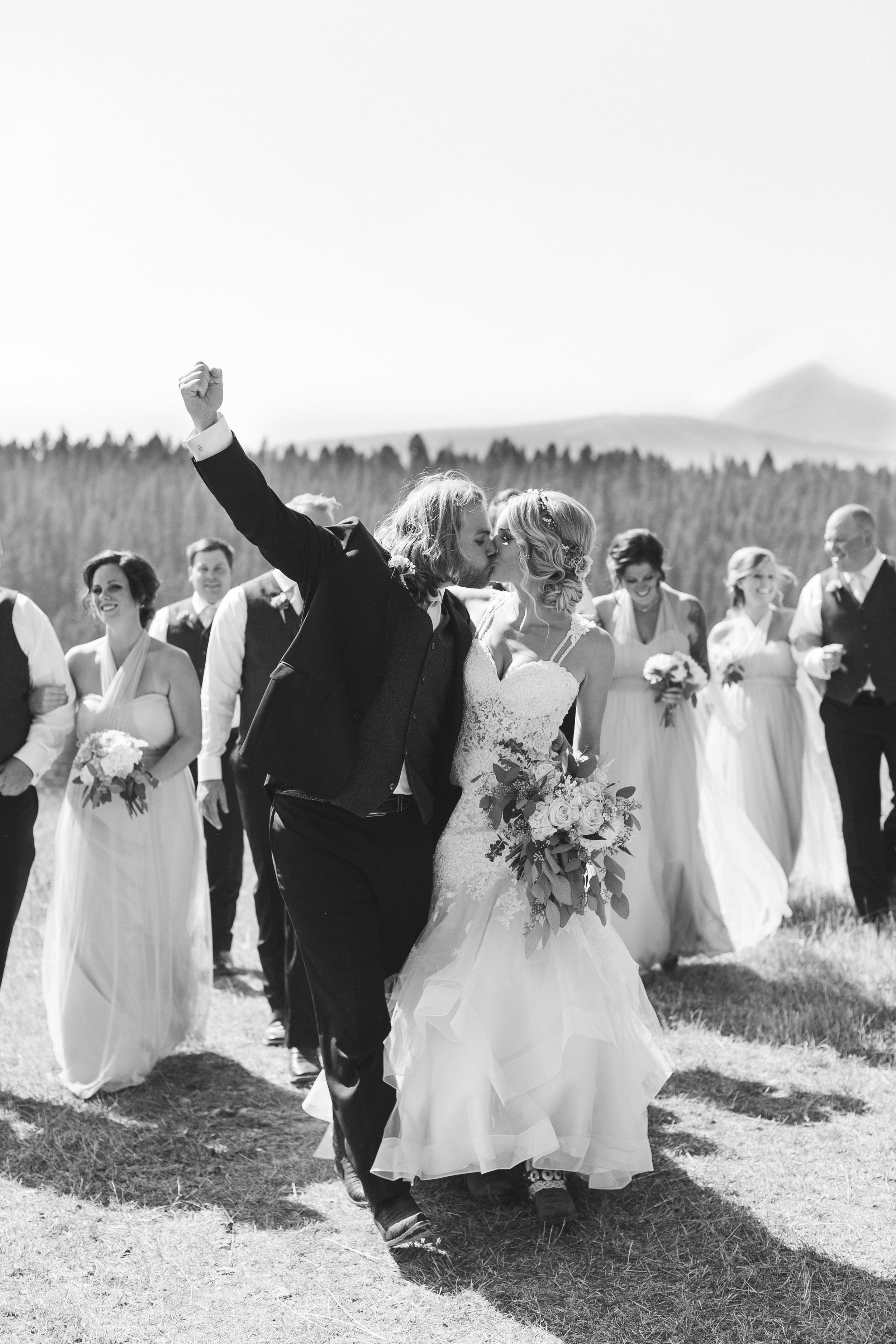 Groom celebrating kiss with bride on mountain for Big Sky Montana wedding at Lone Mountain Ranch with bridal party in background