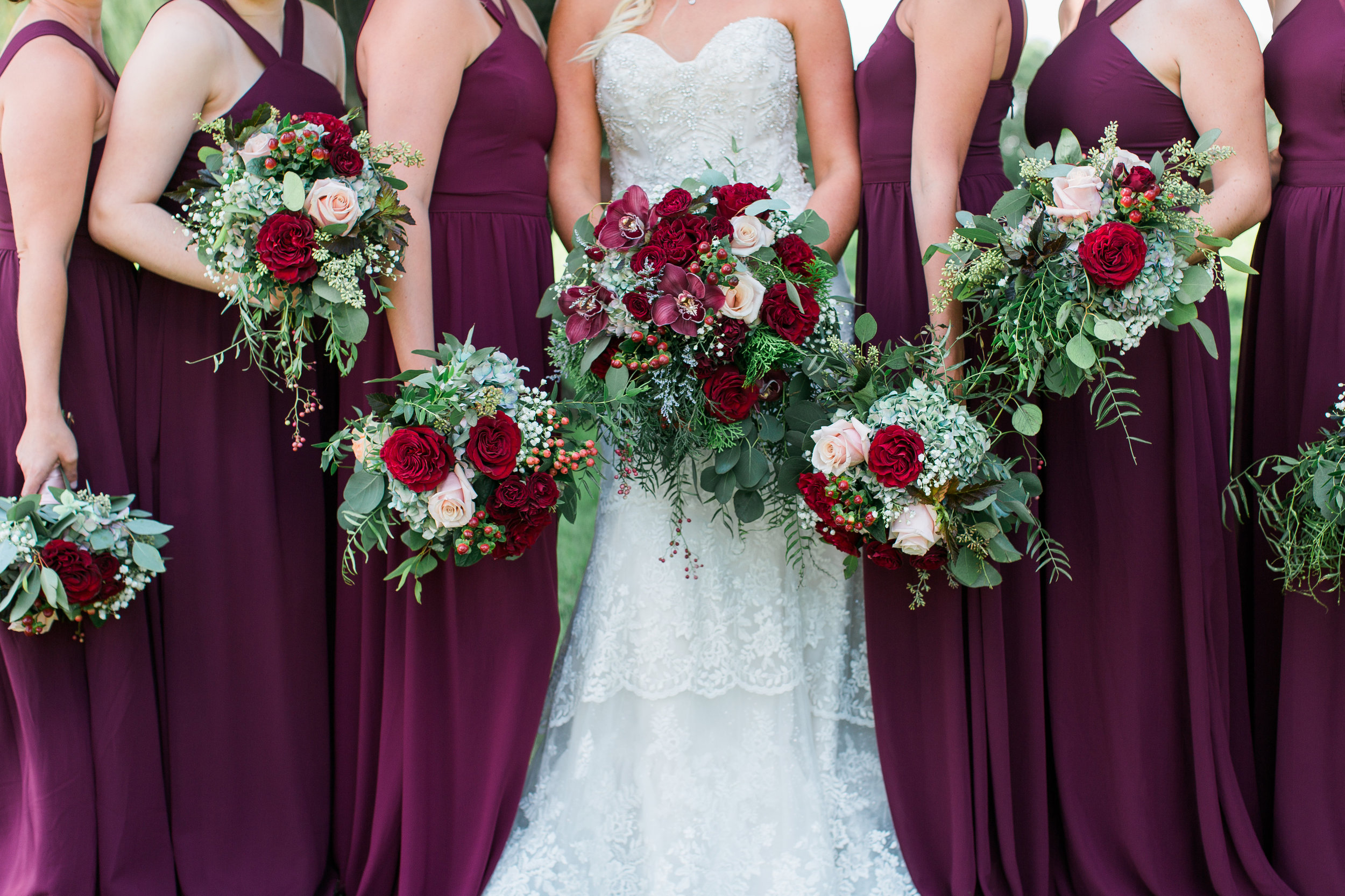 Bridesmaids with maroon wine burgundy dresses and bouquets at Minnesota summer outdoor wedding