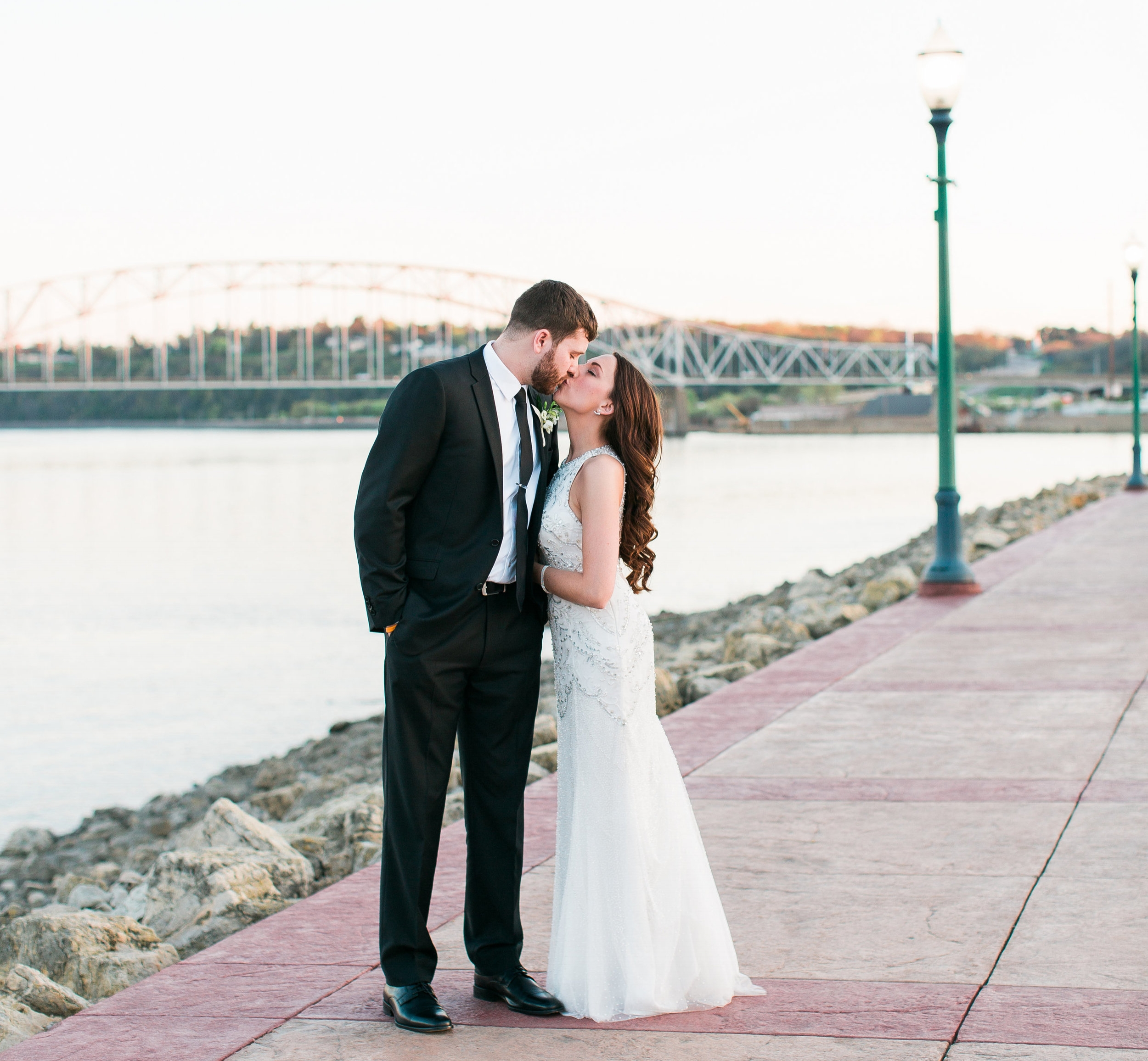 Bride and groom kissing along riverside in Dubuque Iowa