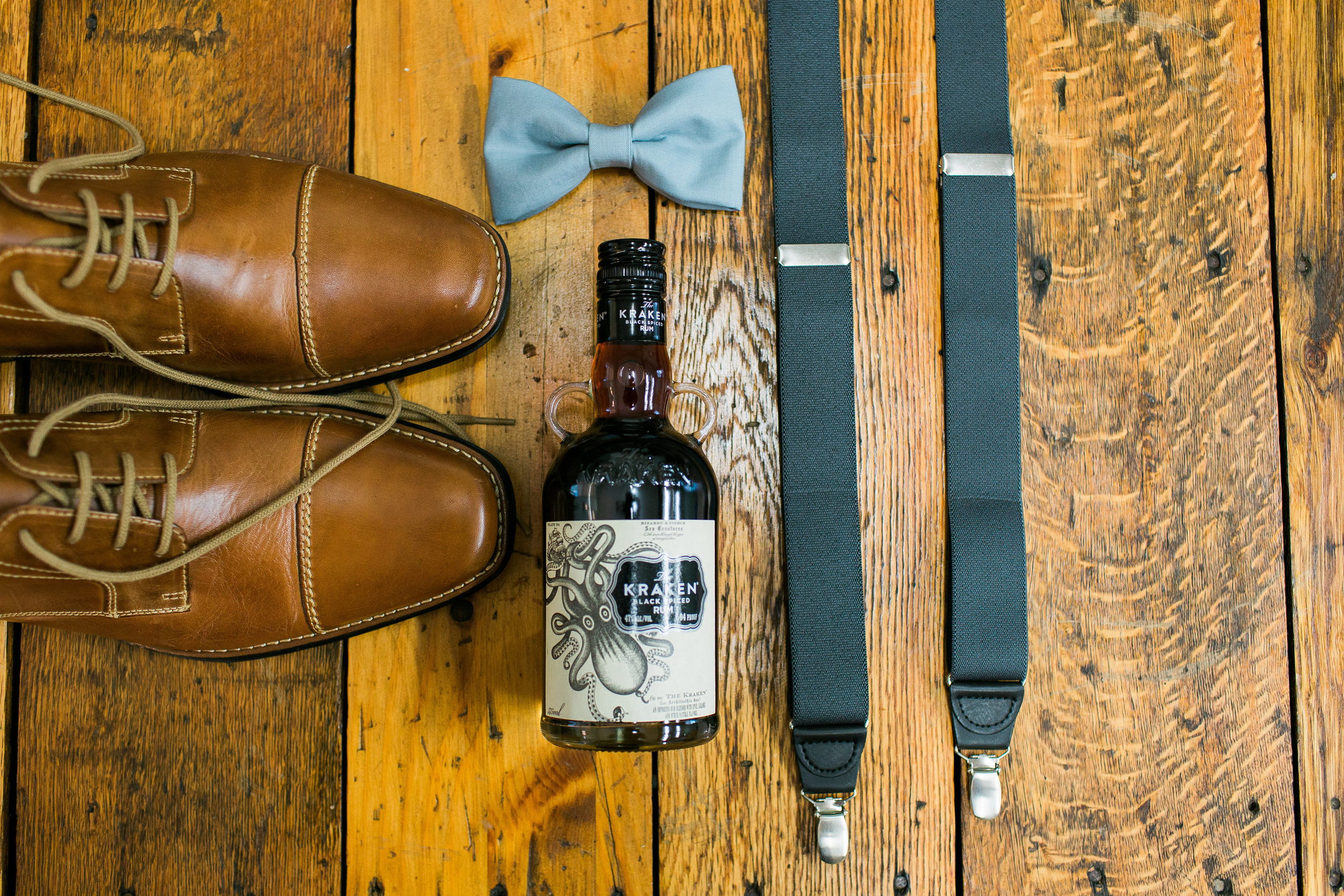 Rustic groom details at The Outpost Center in Chaska Minnesota groom shoes tie and whisky Minnesota wedding photography Mallory Kiesow Photography