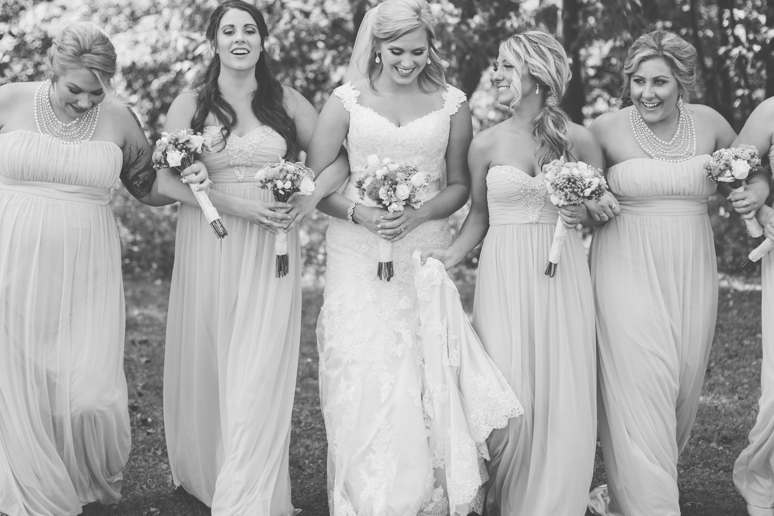 Bride and bridesmaids laughing and walking in Minnesota summer wedding black and white photo Minnesota wedding photography Mallory Kiesow Photography