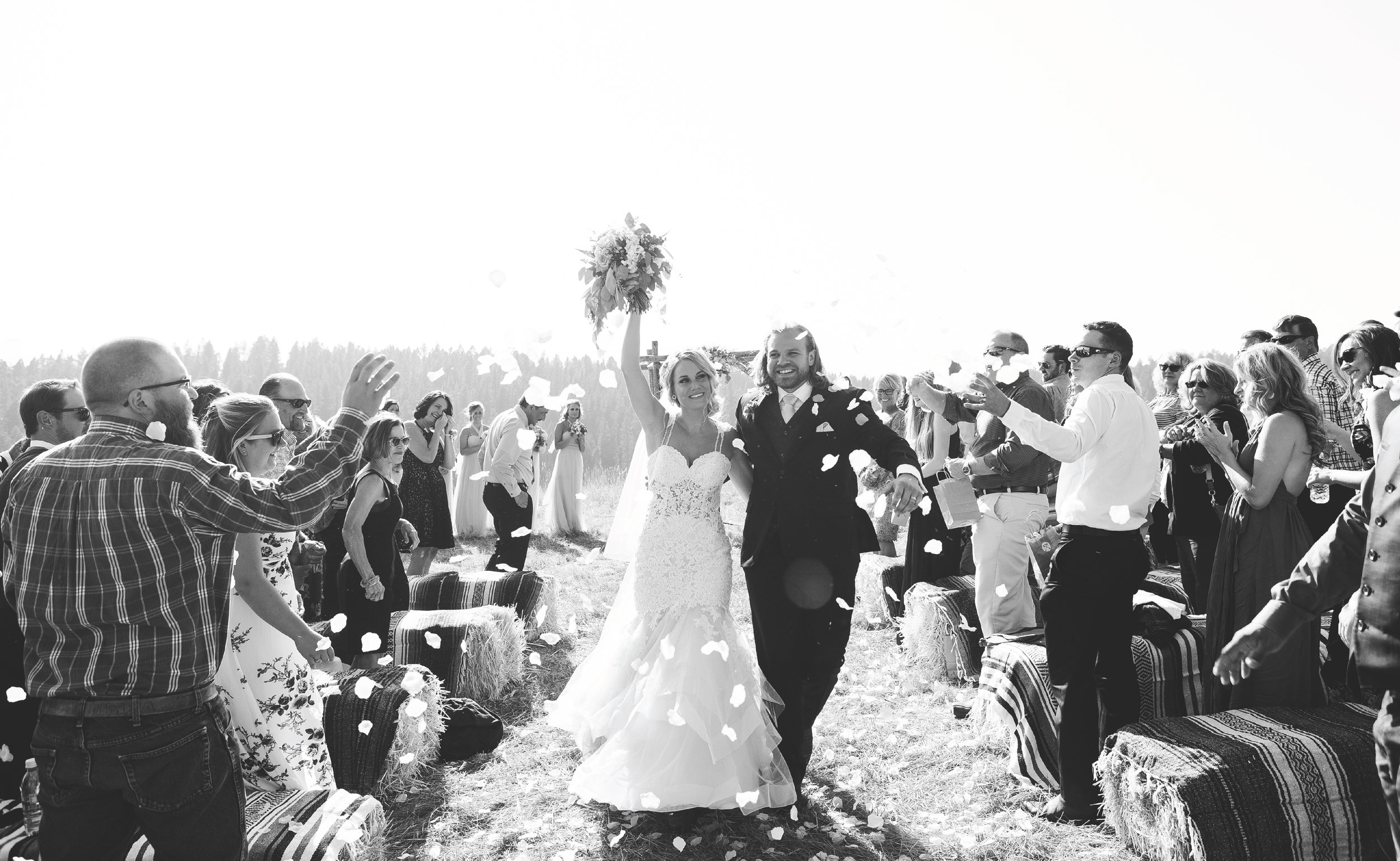Bride and groom exiting ceremony celebrating with confetti black and white mountainside Montana wedding Lone Mountain Ranch Minnesota wedding photographer Mallory Kiesow Photographhy