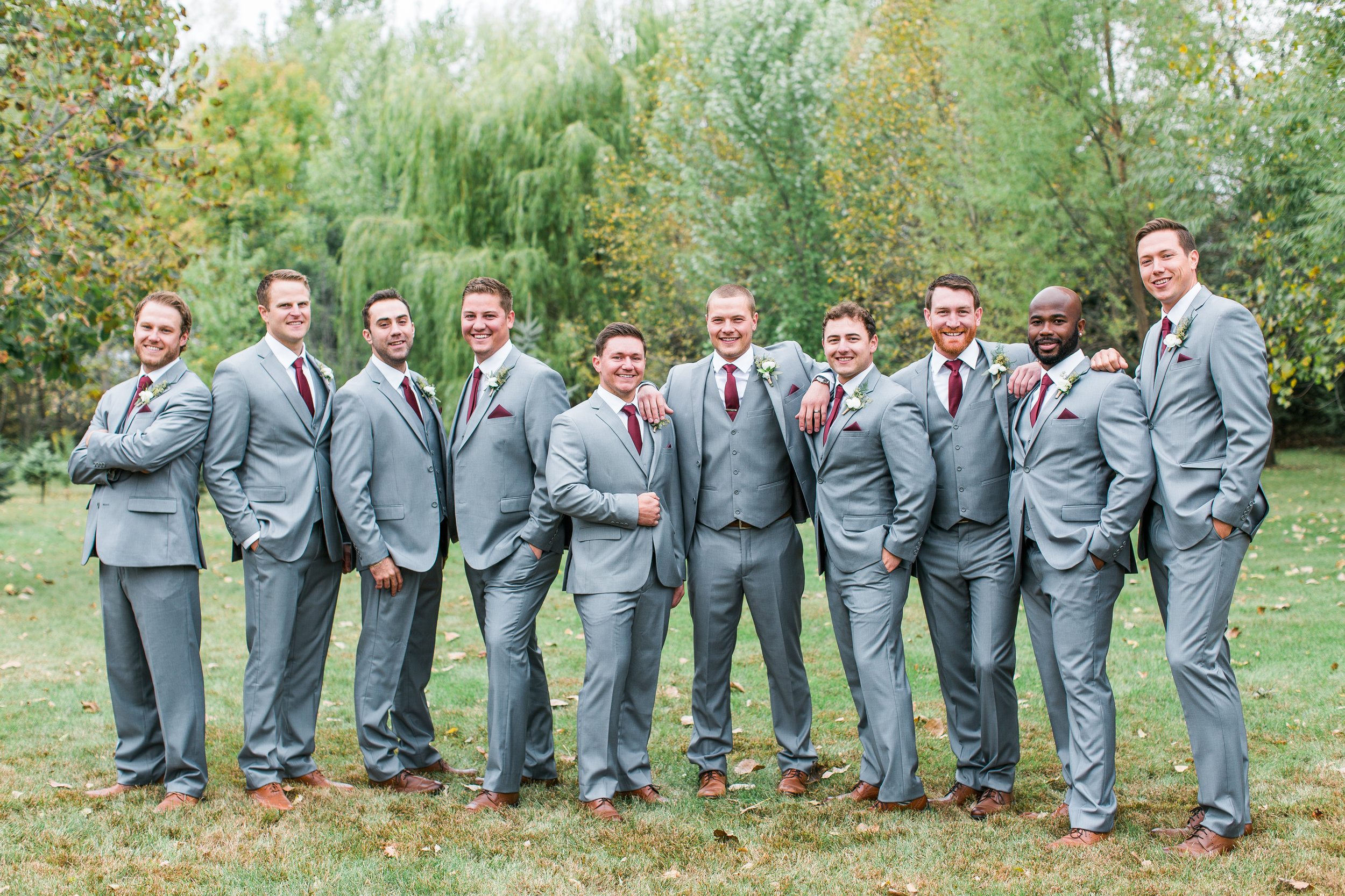 Groomsmen in gray suits with burgundy accents casual pose Minnesota backyard fall wedding Minnesota wedding photography Mallory Kiesow Photography