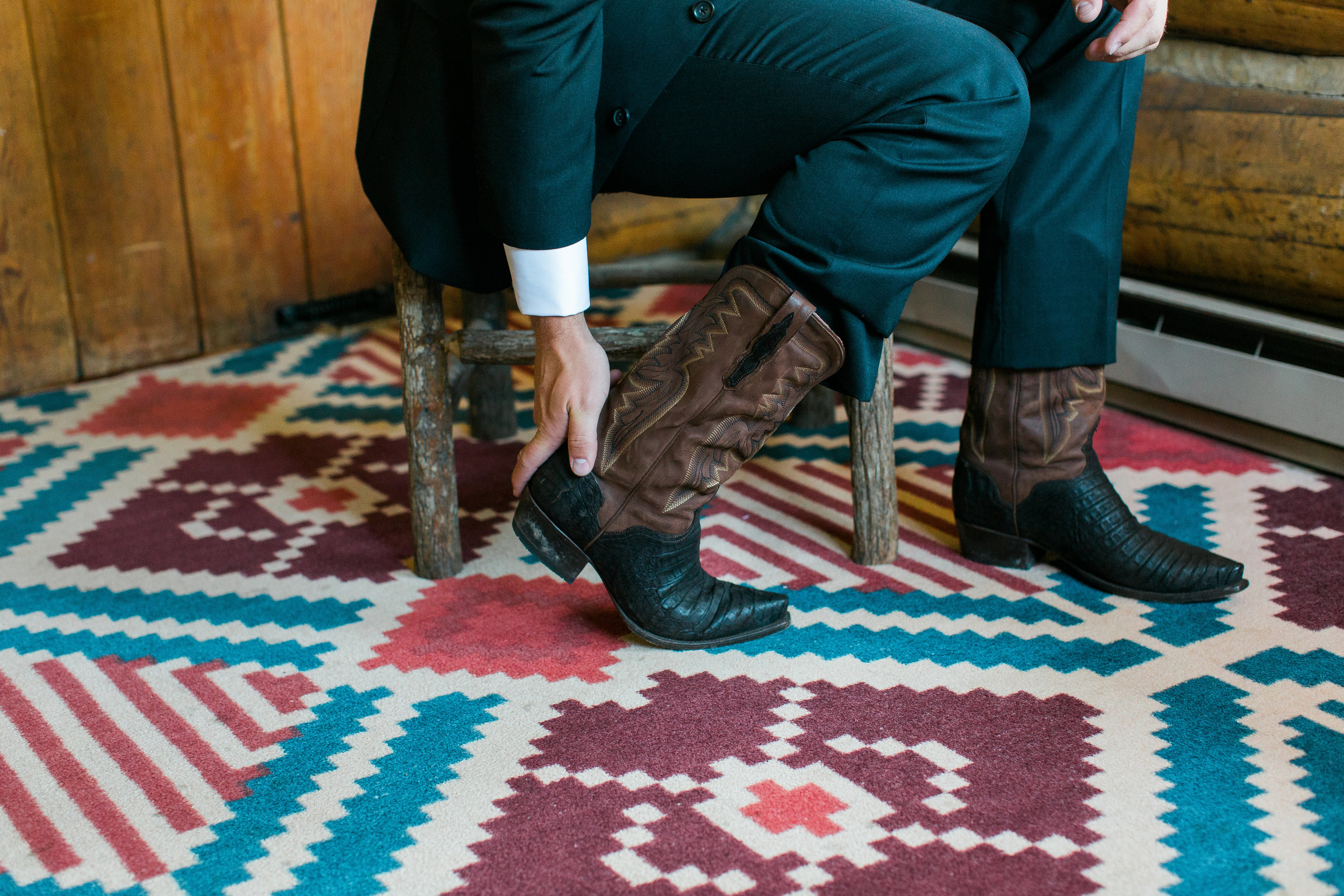 Rustic southwestern groom putting on cowboy boots Montana Big Sky Lone Mountain Ranch wedding Minnesota wedding photography Mallory Kiesow Photography