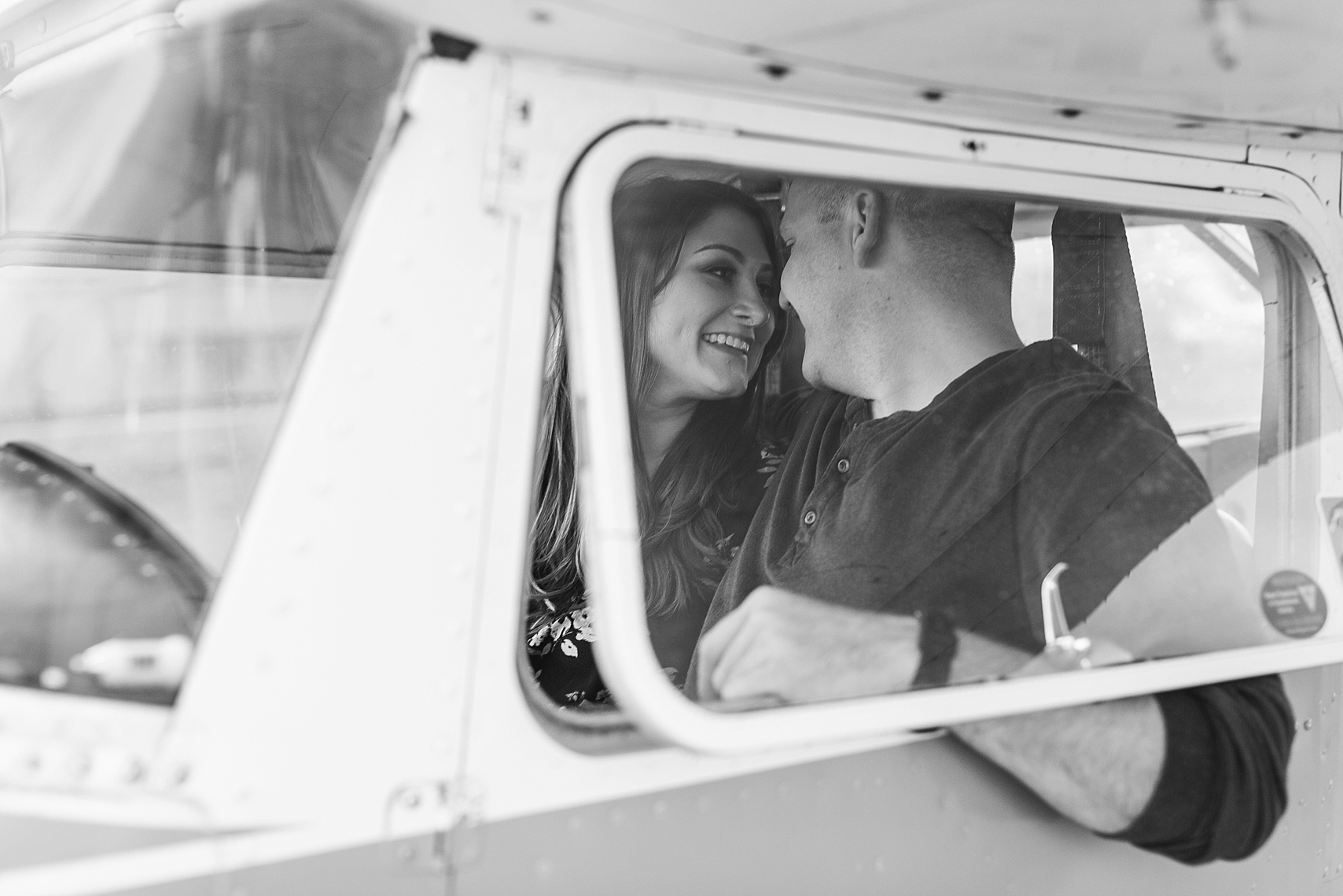 Minnesota airplane engagement session flying cloud airport black and white couple in window