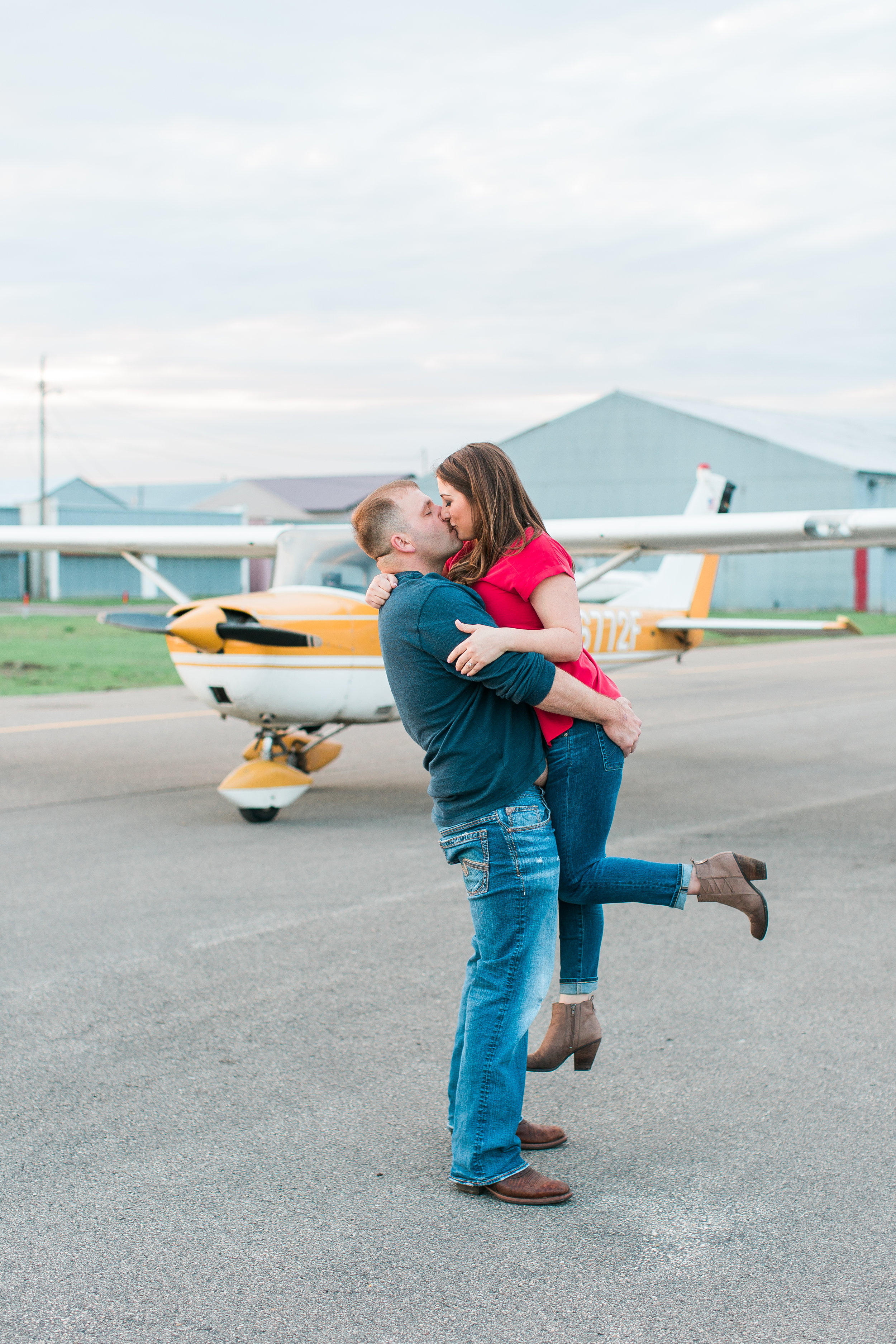 Engaged couple kissing and guy holding girl in front of airplane at Flying Cloud Airport in Eden Prairie for engagement session Minnesota engagement photographer Mallory Kiesow Photography