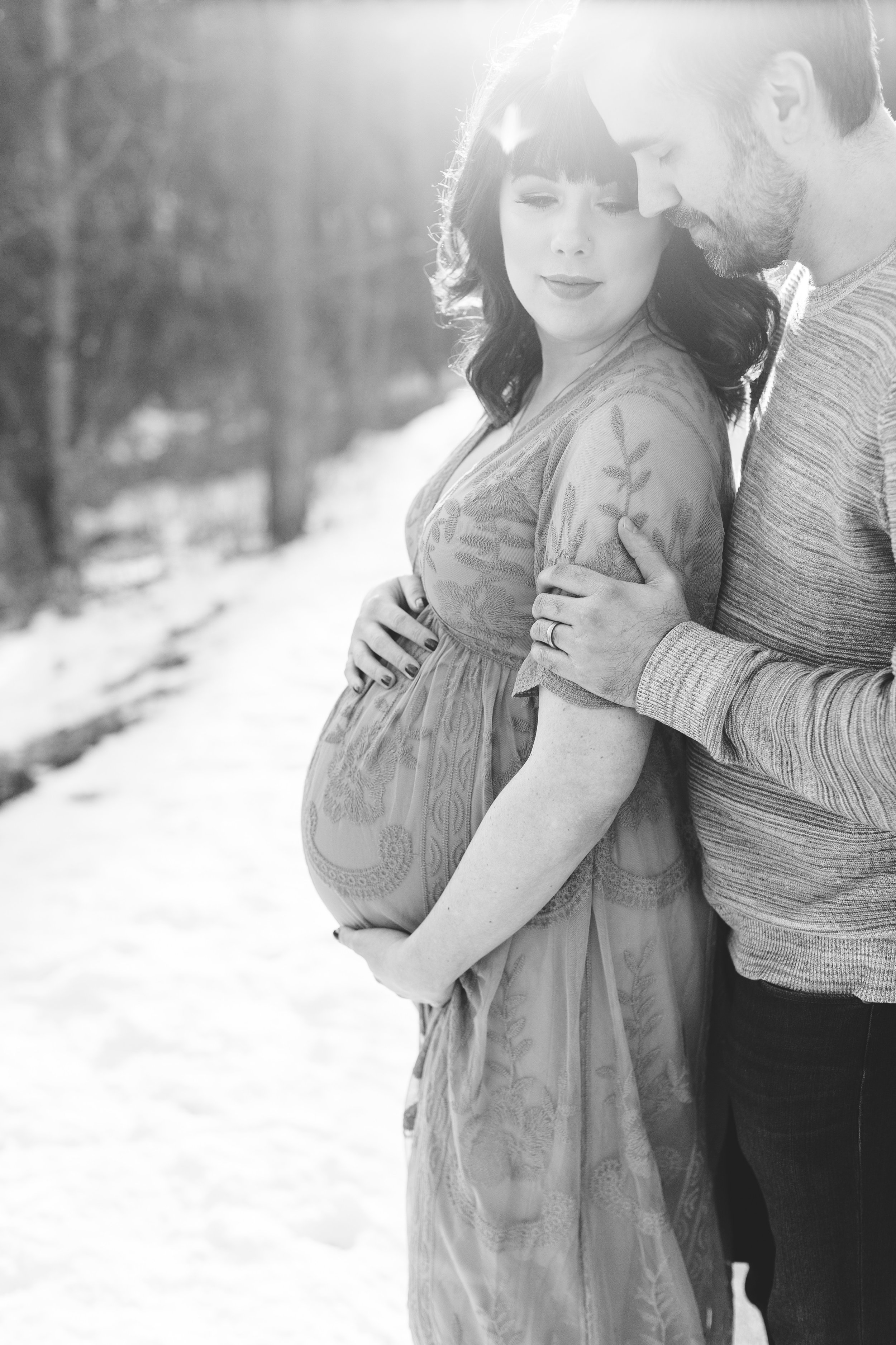 Pregnant mom and dad to be in black and white photo holding belly in winter maternity session Minnesota maternity photographer Mallory Kiesow Photography