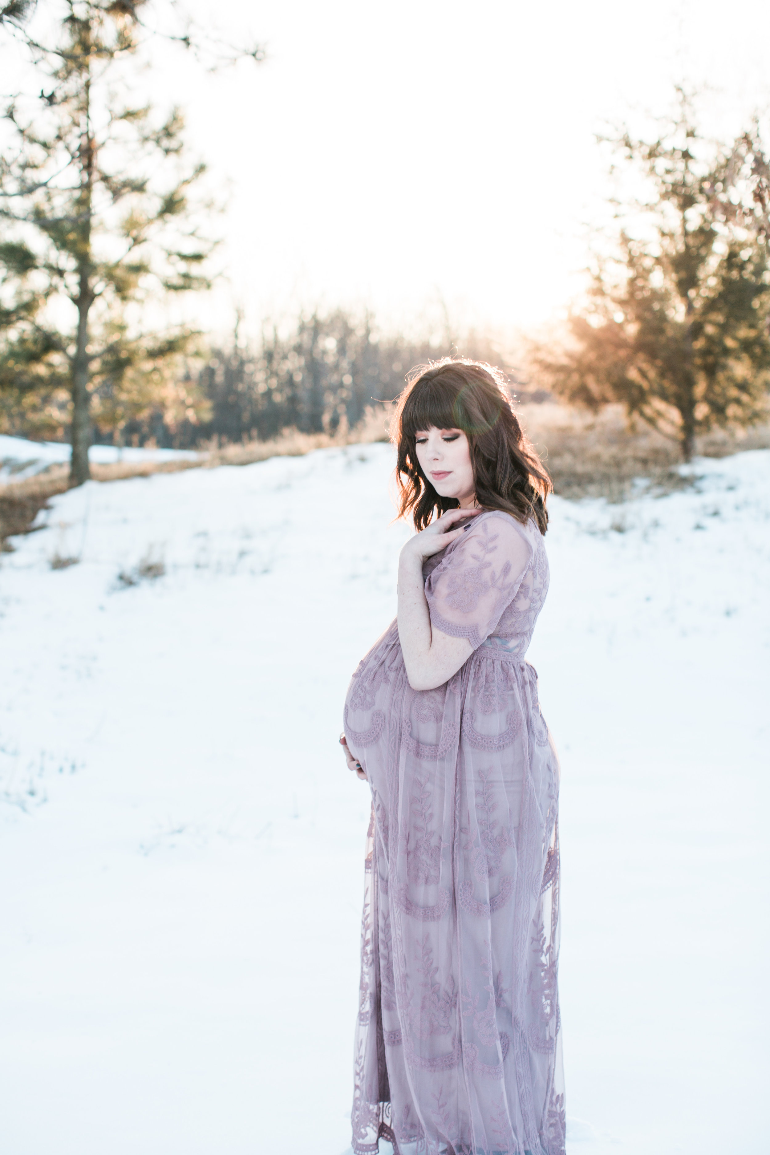 Expecting mother in pink lace dress in winter maternity photos at sunset Minnesota maternity photographer Mallory Kiesow Photography