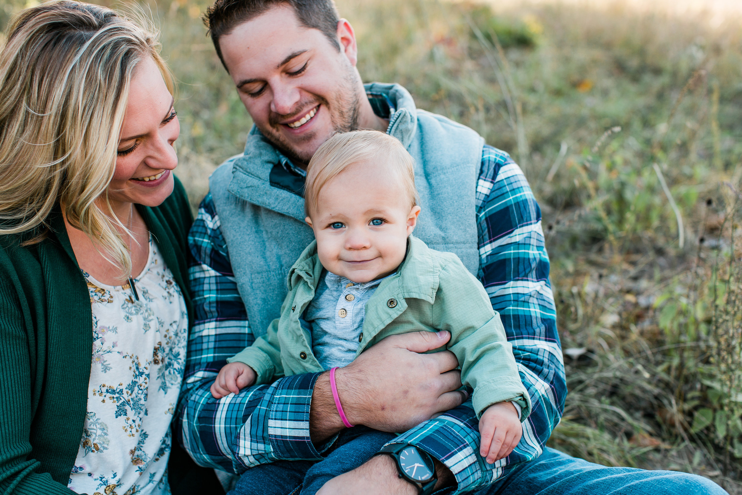 Family of mom dad and baby boy sitting in fall family session Minnesota family photographer Mallory Kiesow Photography