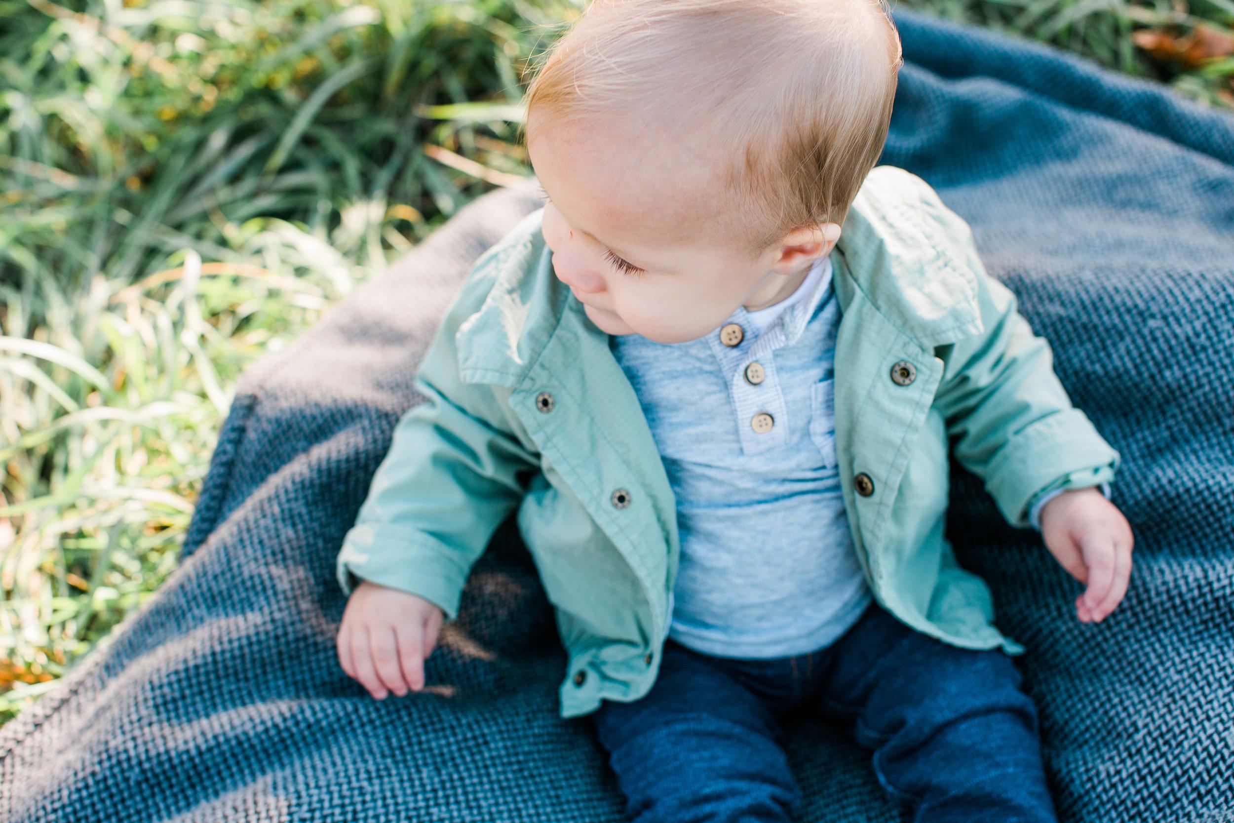 Blone baby boy portrait with green jacket jeans and long eyelashes Minnesota family photographer Mallory Kiesow Photography