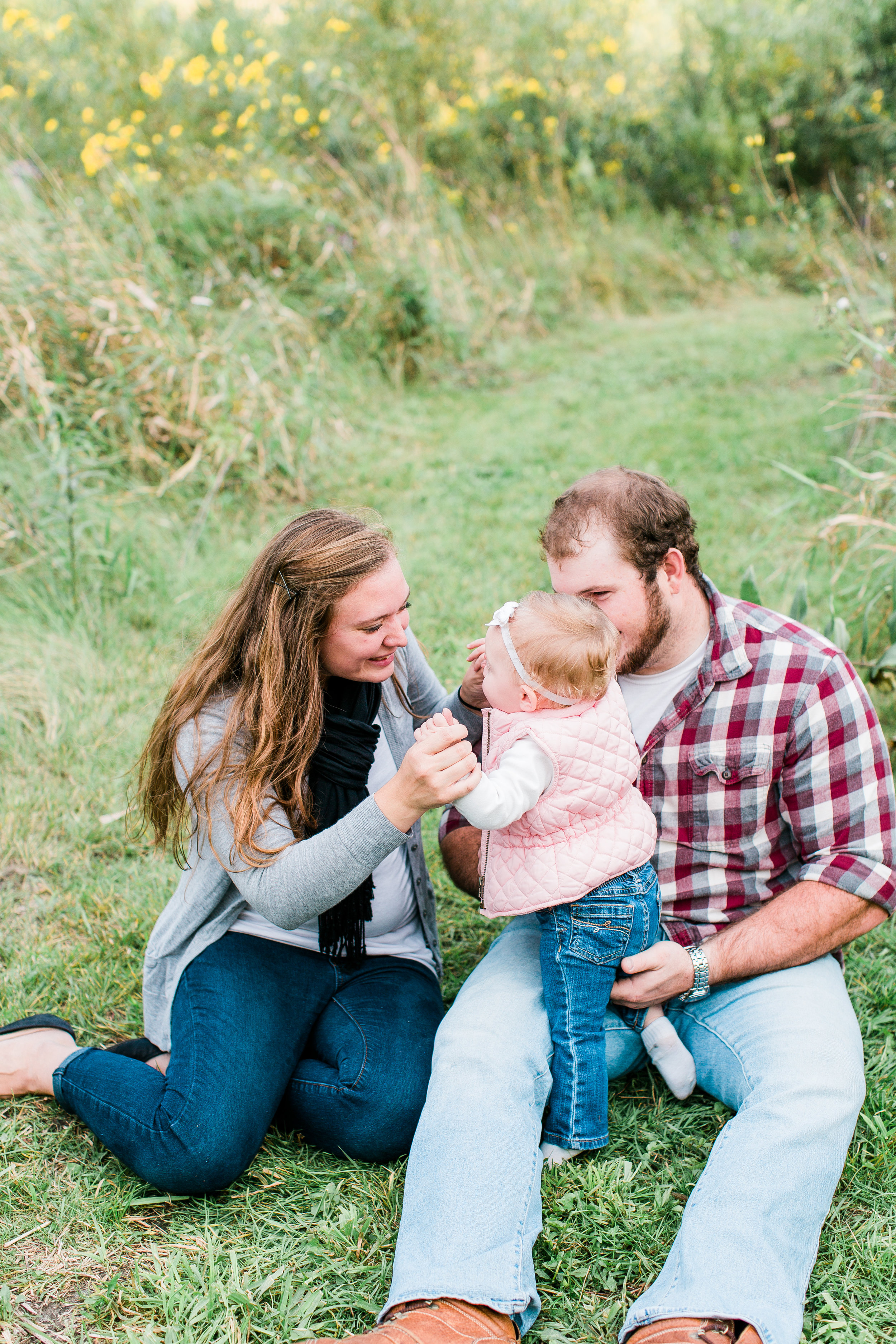 Mom, Dad, and baby sitting playing in the grass in Minnesota summer family session Minnesota family photographer Mallory Kiesow Photography